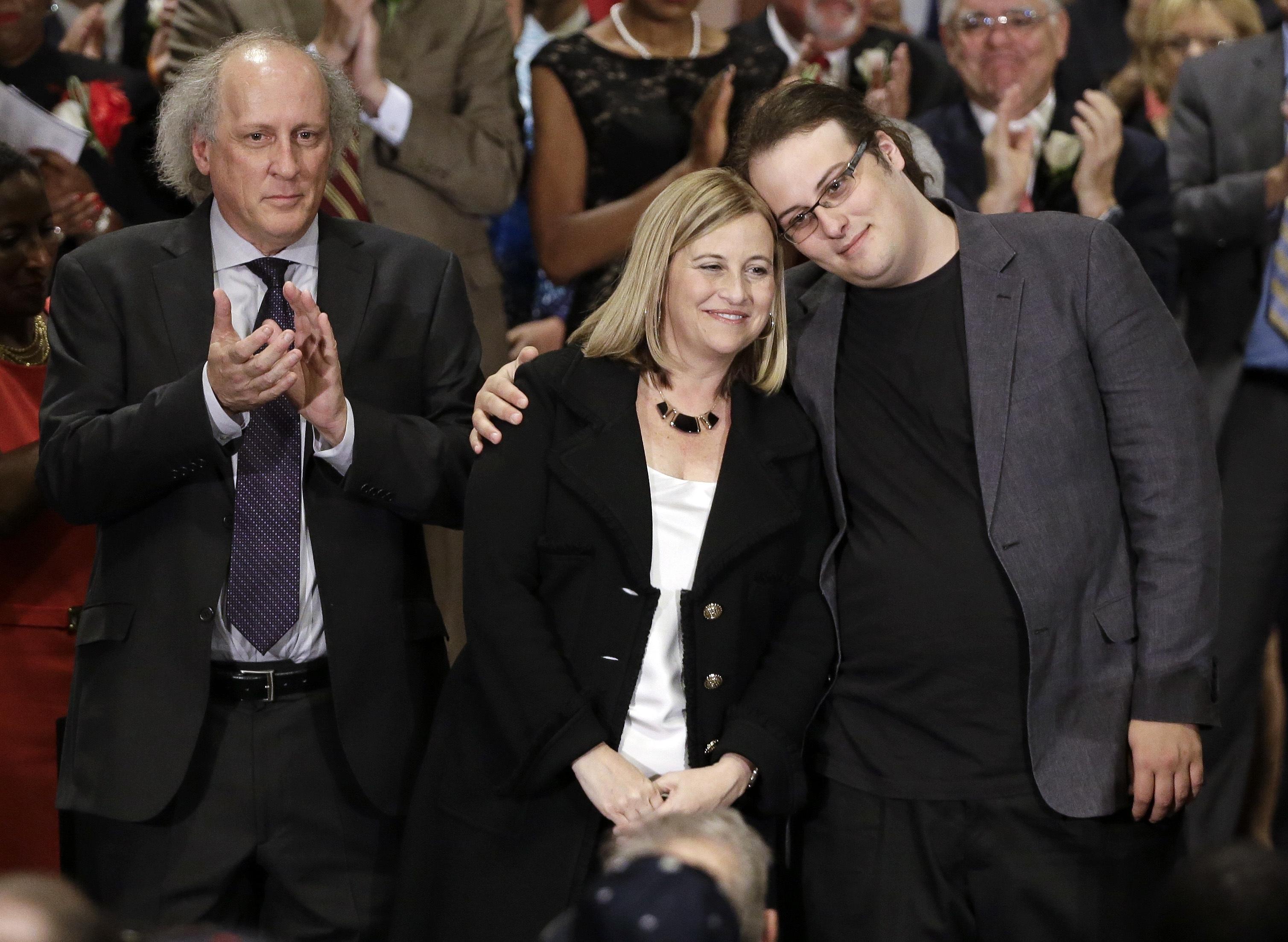 Nashville Mayor Megan Barry, center, is hugged by her son, Max, as her husband, Bruce, left, applauds after she was sworn into office in Nashville, Tenn., on Sept. 25, 2015