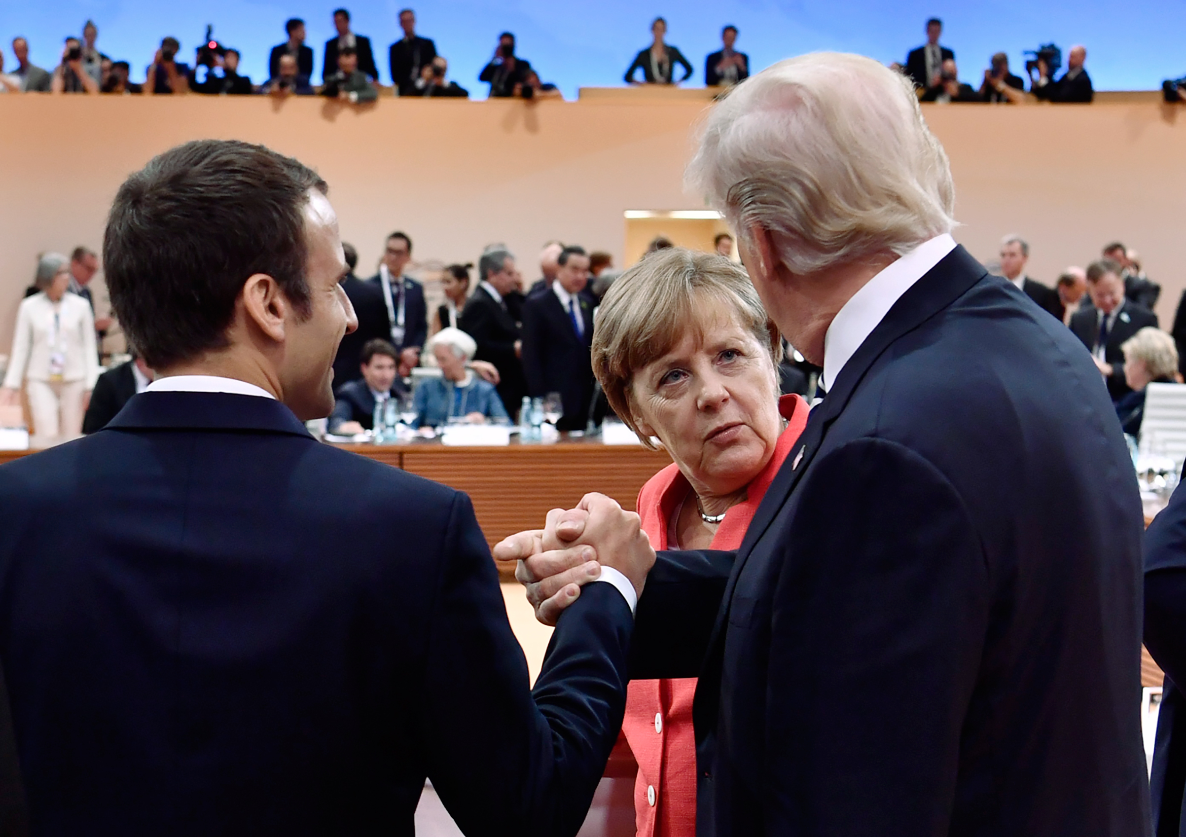 Macron, left, and Trump, right, chat with Merkel in Hamburg on July7