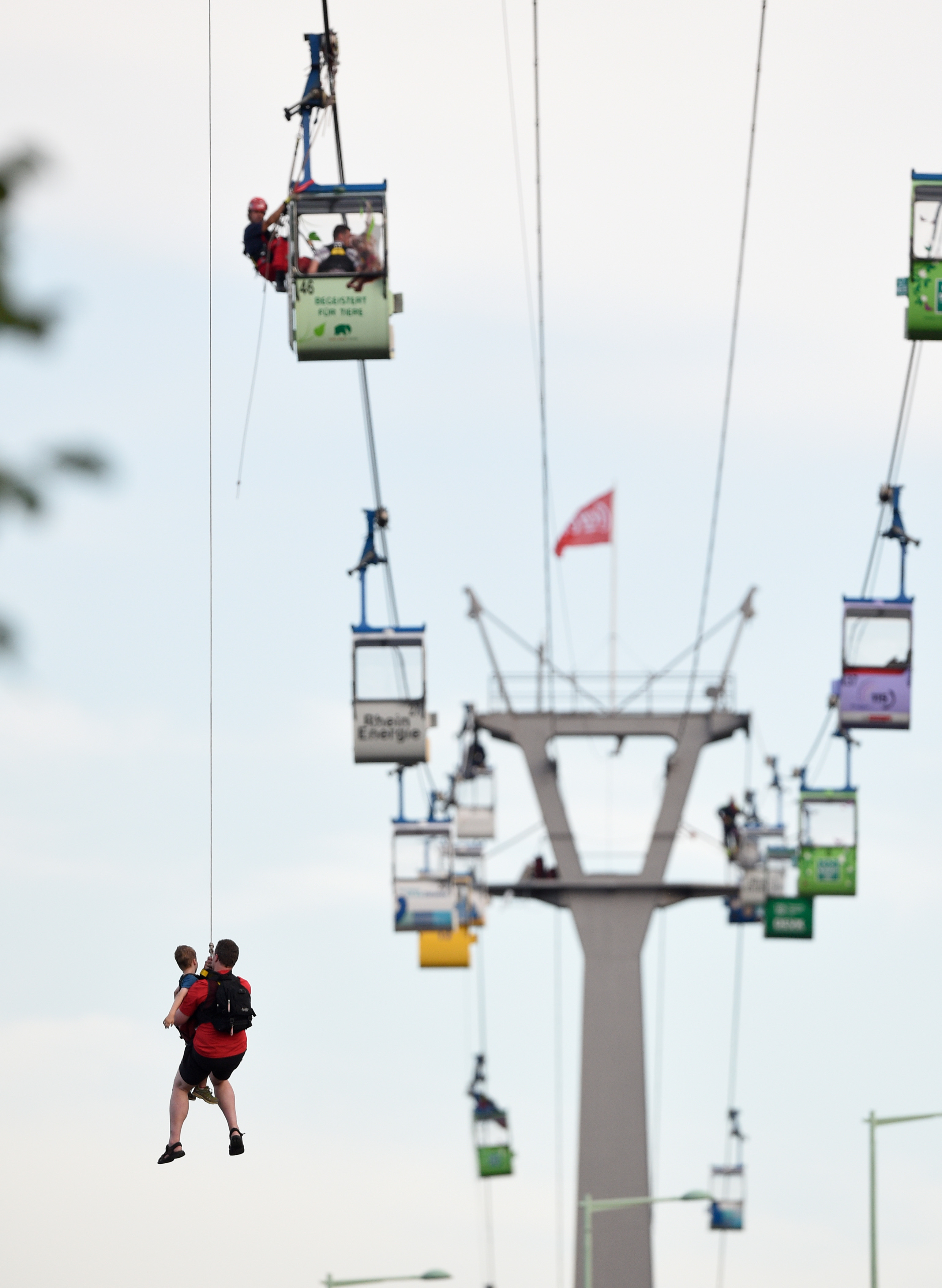 father and his child are abseiled from a gondola over the Rhine in Cologne. Rainer Jensen - AFP / Getty Images.