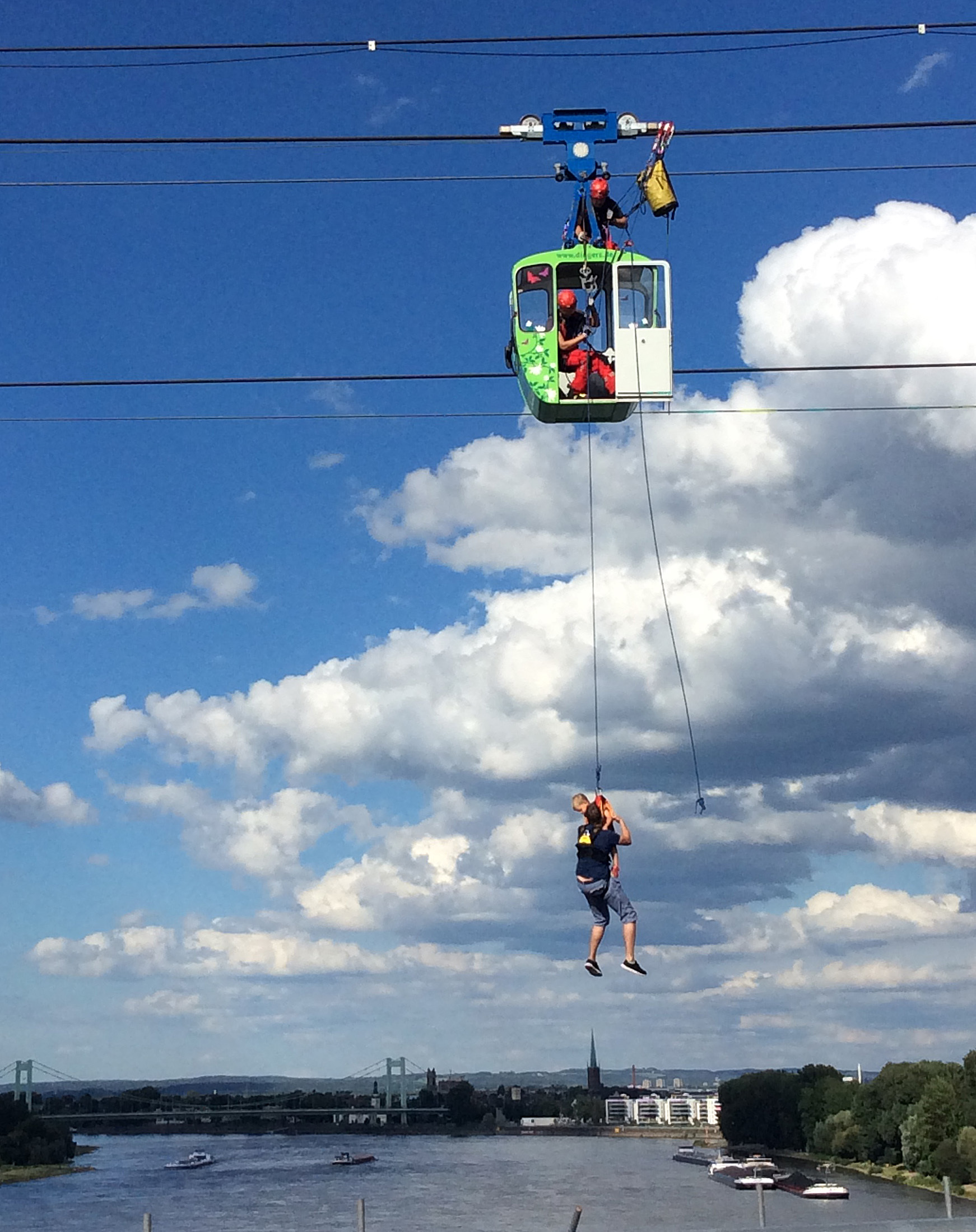 A father and his child are abseiled from a gondola over the Rhine in Cologne, western Germany, on July 30, 2017. Martin Oversohl -AFP / Getty Images
