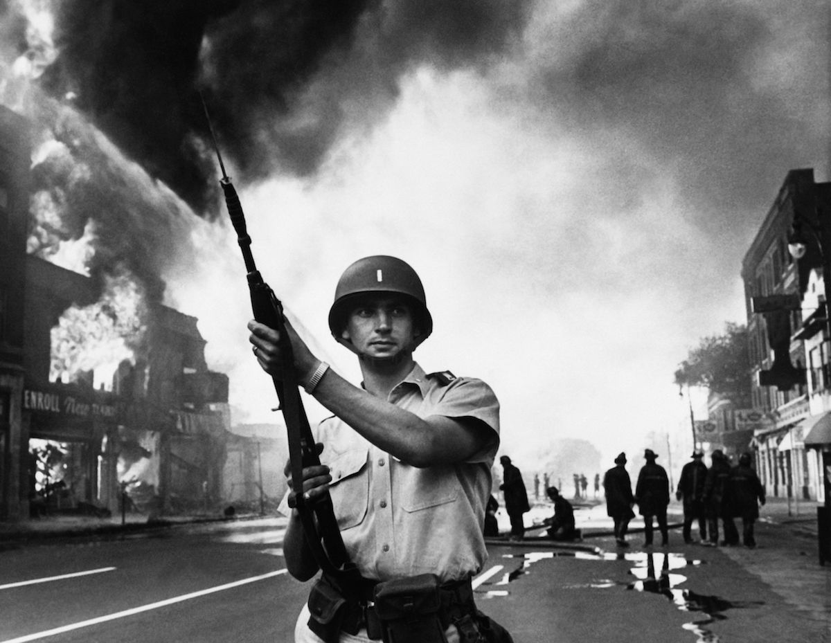 A federal soldier stands guard in a Detroit street on July 25, 1967, as buildings are burning during riots that erupted in Detroit following a police operation