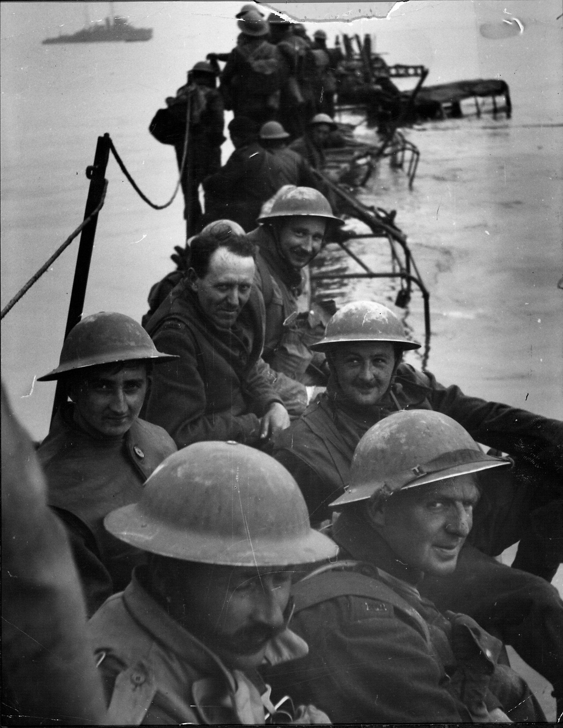Members of Royal Ulster Rifles waiting on improvised pier of lorries to evacuate Dunkirk during low tide.