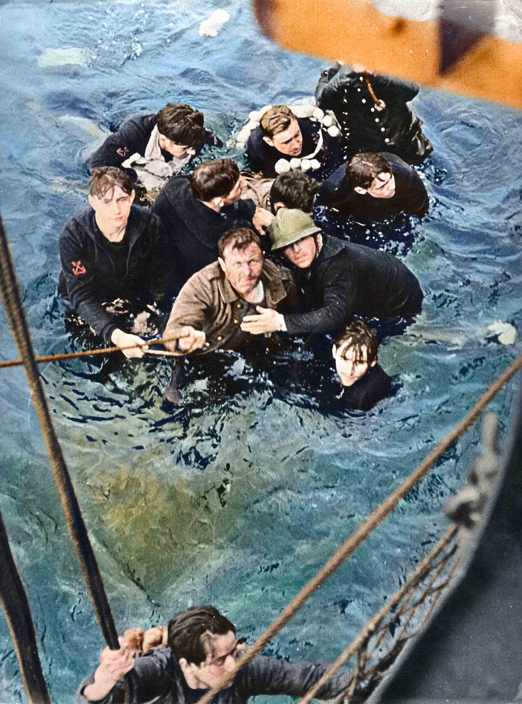 Crew members of the French destroyer Bourrasque, sunk by mine at Dunkirk, are hauled aboard a British vessel from their sinking life-raft.