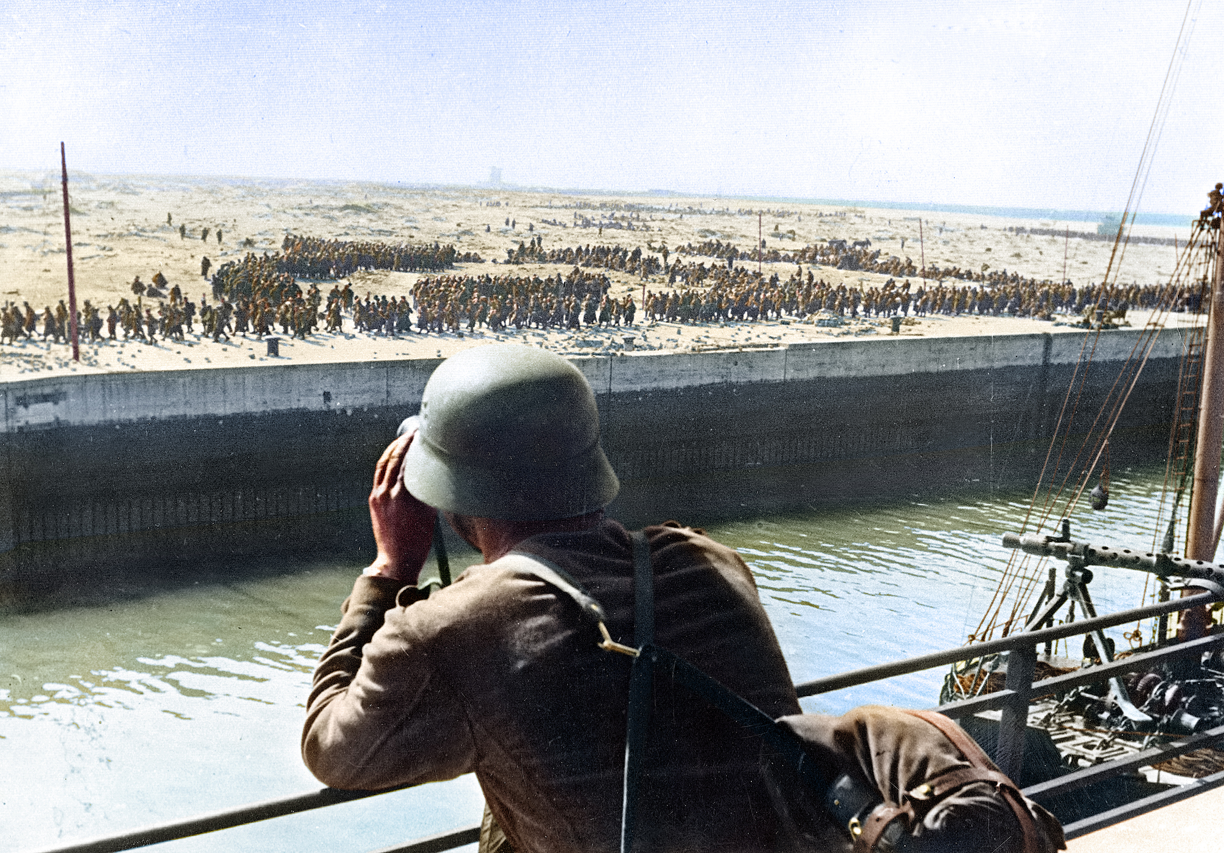 A member of the German Wehrmacht looks through a pair of binoculars on French and British prisoners of war in the harbour of Dunkirk on the Western Front in France in June 1940.
