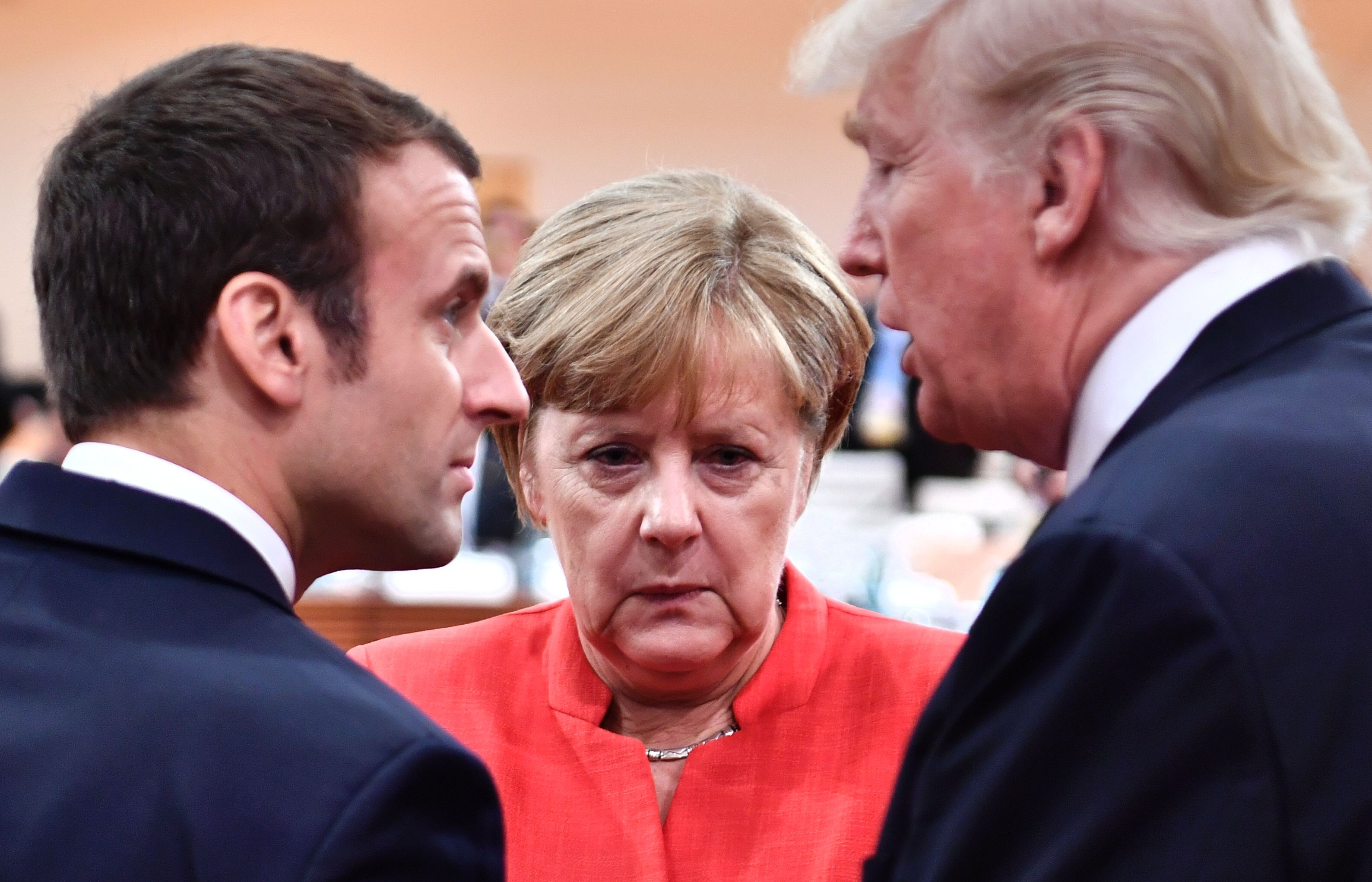 French President Emmanuel Macron, German Chancellor Angela Merkel and U.S. President Donald Trump confer at the start of the first working session of the G20 meeting in Hamburg, Germany, on July 7, 2017.