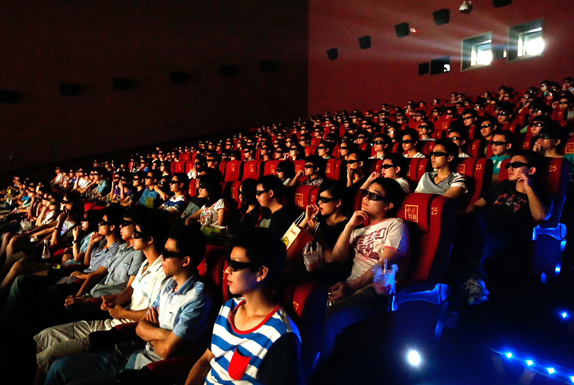 An audience watches  Transformers - Age Of Extinction  through 3D glasses at a cinema on June 27, 2014 in Wuhan, Hubei province, China.