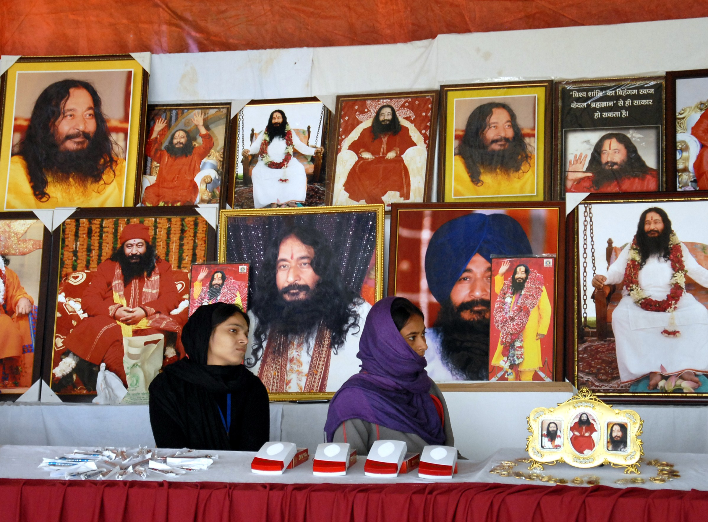 Indian followers of deceased guru Ashutosh Maharaj Divya Jyoti Jagriti Sansthaan sit front posters bearing his image on Dec. 14, 2014.