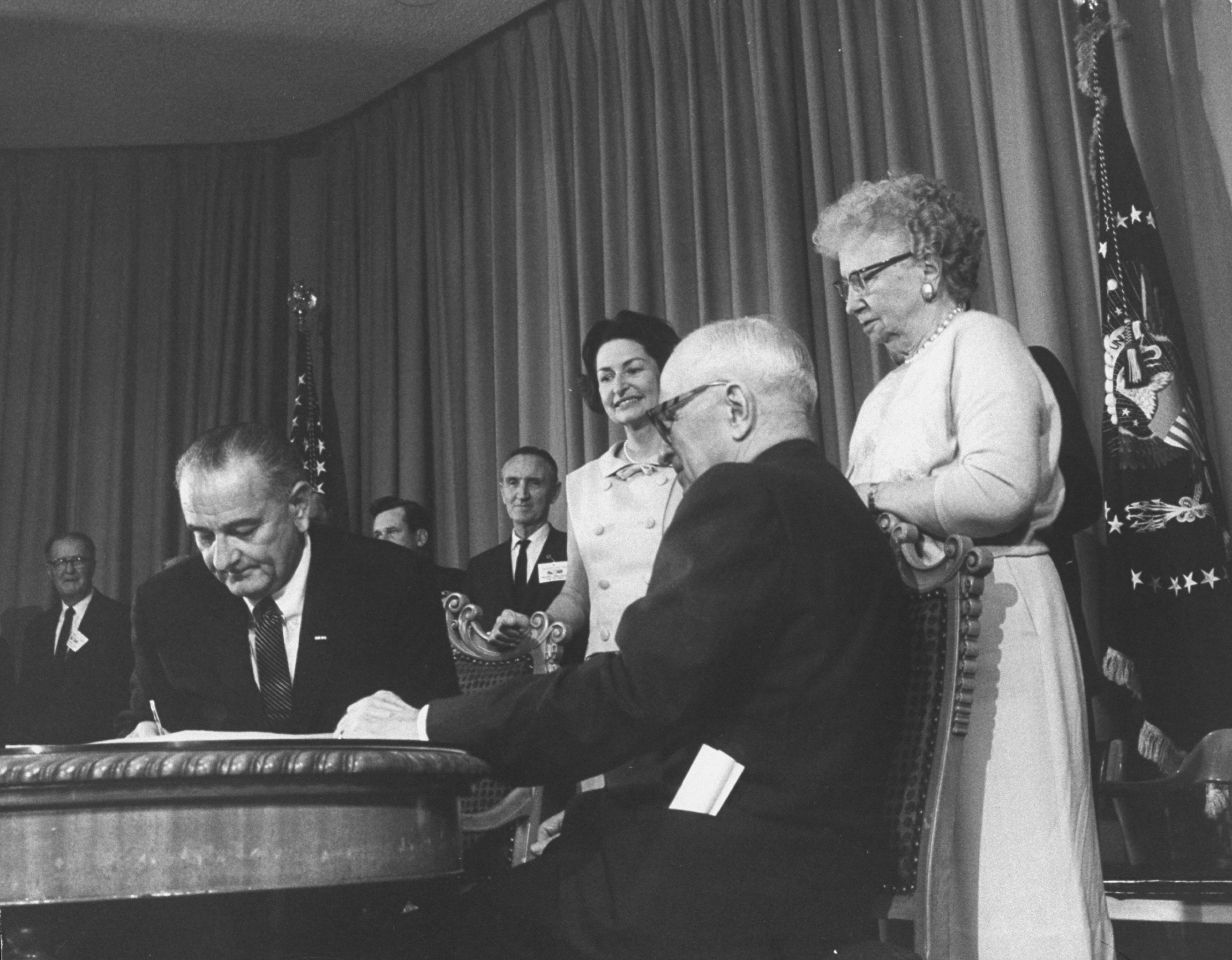 (L-R) Pres. Lyndon B. Johnson, Lady Bird Johnson, Harry S. Truman, and Bess Truman at signing of Medicare bill on July 30, 1965, at the Harry S. Truman Library & Museum in Independence, Missouri.