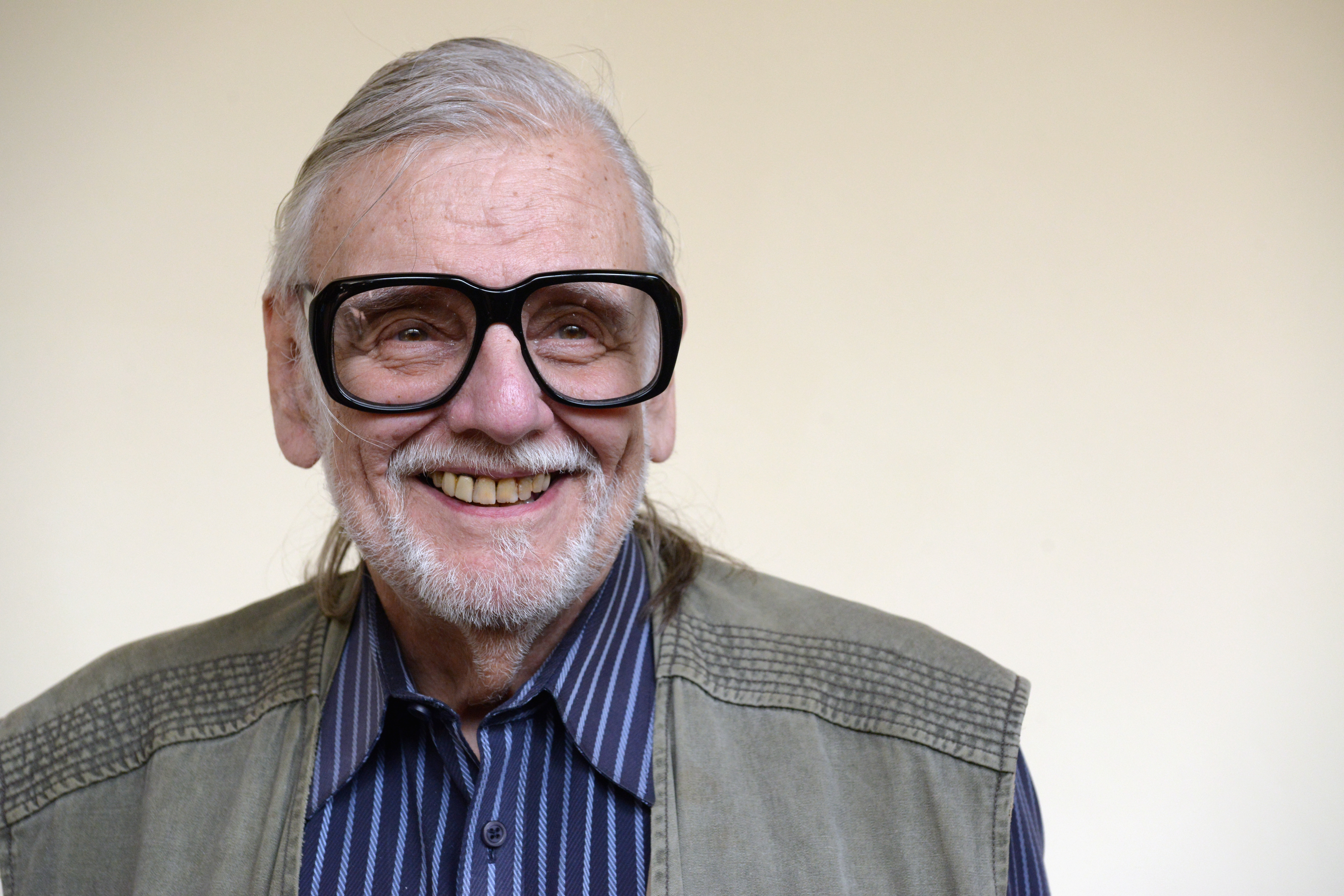 American film Director, screen writer and editor George Romero poses for a photo after attending a press conference during the Lucca Film Festival 2016 on April 7, 2016 in Lucca, Italy.