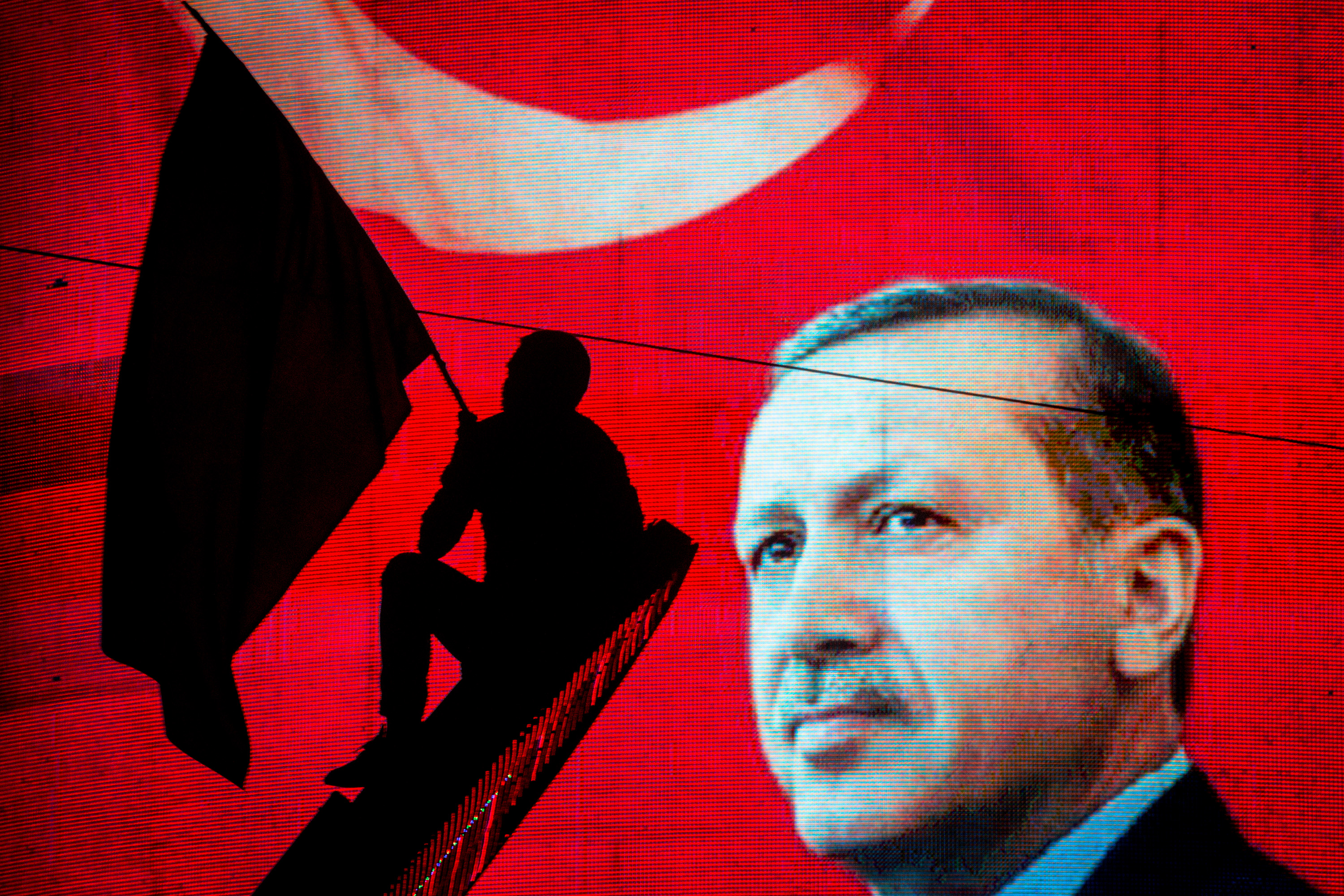A supporter of Turkish President Recep Tayyip Erdogan waves a flag against an electronic billboard during a rally in Kizilay Square on July 18, 2016 in Ankara, Turkey.