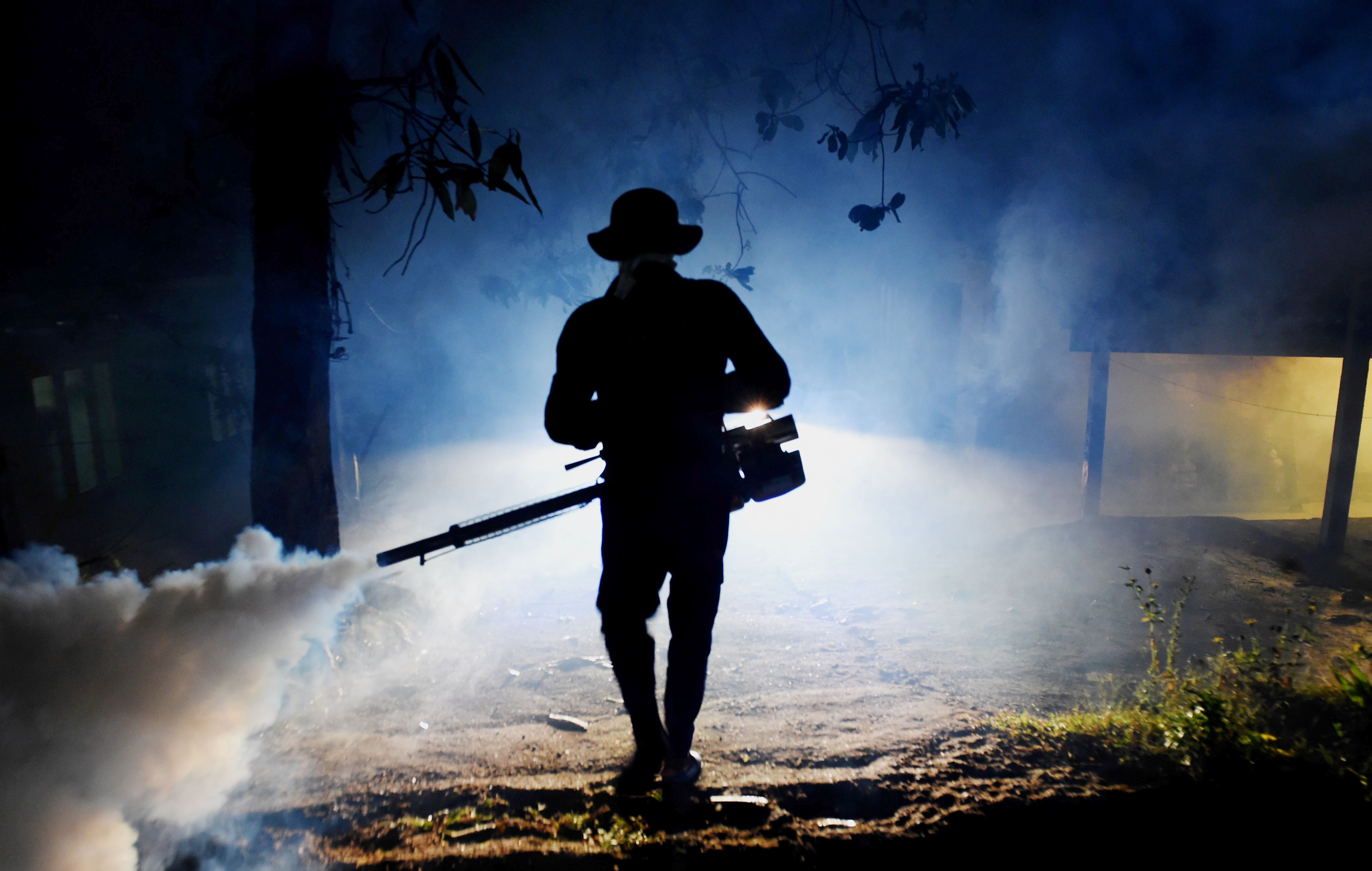 In this Jan. 24, 2017 photo, a Sri Lankan health worker sprays a neighborhood with a fog used to ward off mosquitos in Biyagama on the outskirts of Colombo.