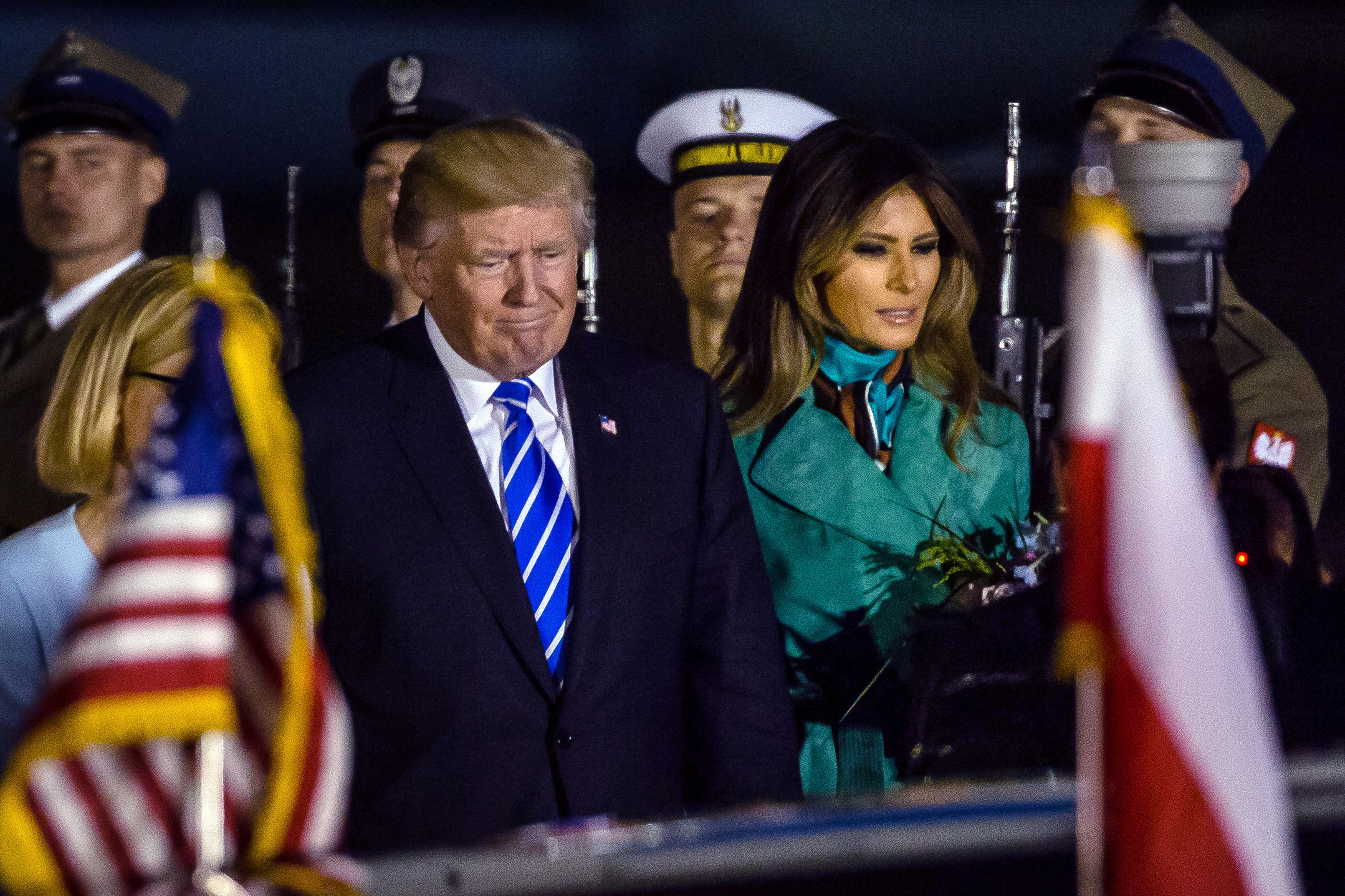 US President Donald Trump (L) and US First Lady Melania Trump (R) react after stepping off Air Force One upon their arrival at Chopin Airport in Warsaw,on July 5, 2017