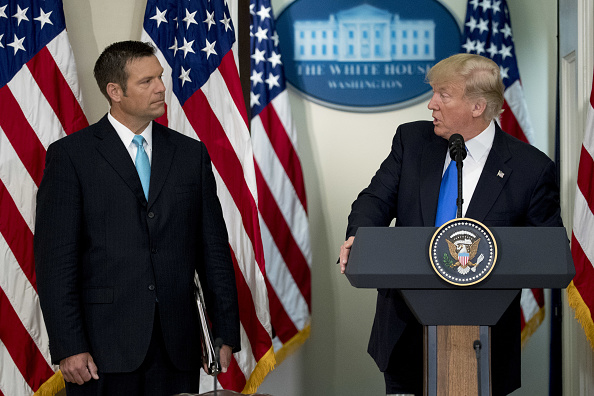 President Trump speaks as Kris Kobach, Kansas's Secretary of State, listens during the initial meeting of the Presidential Advisory Commission on Election Integrity at the Eisenhower Executive Office Building in Washington, D.C., on July 19, 2017.