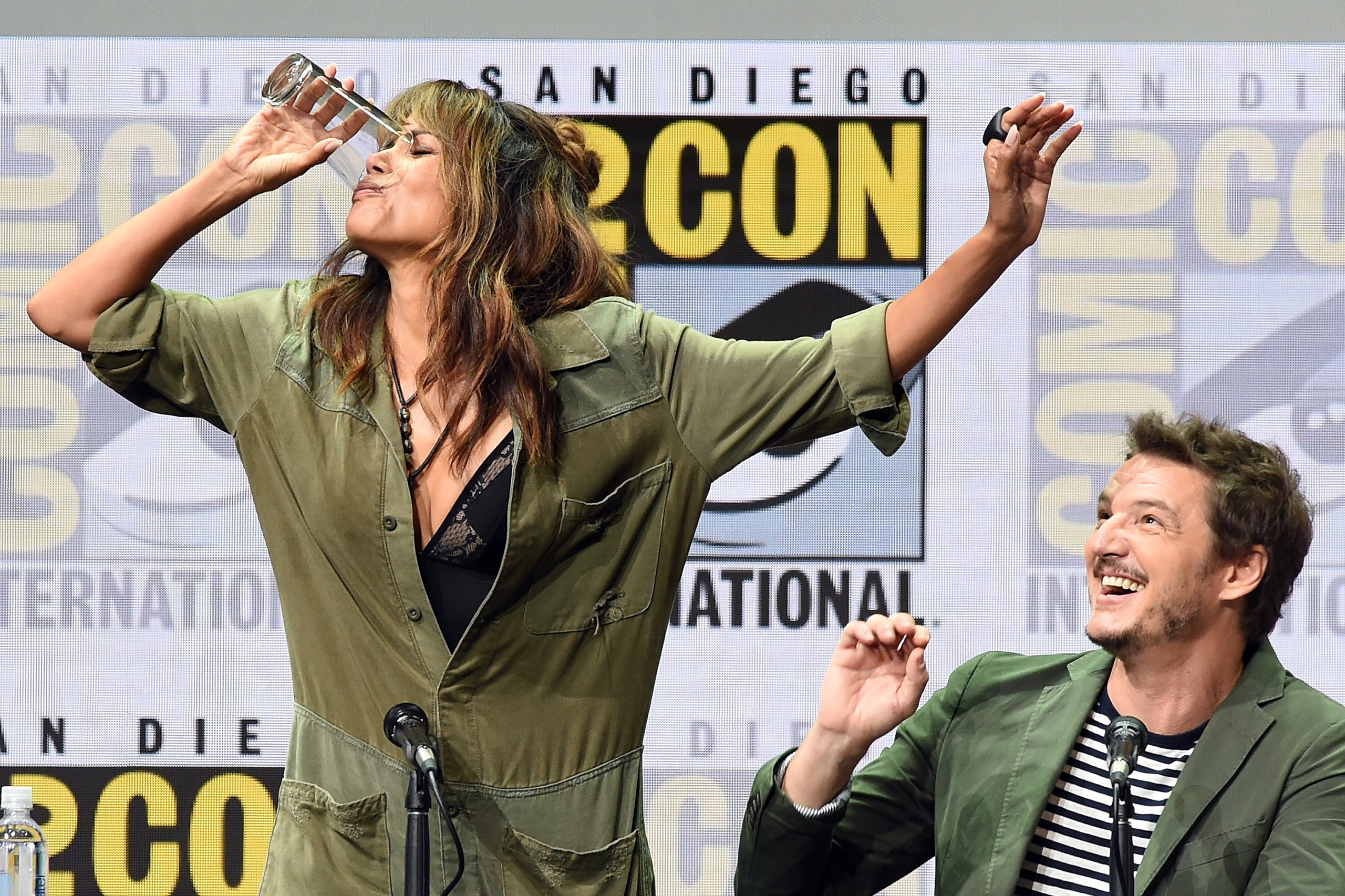 Actor Halle Berry takes a drink onstage while actor Pedro Pascal looks on at the 20th Century FOX panel during Comic-Con International 2017 at San Diego Convention Center on July 20, 2017.