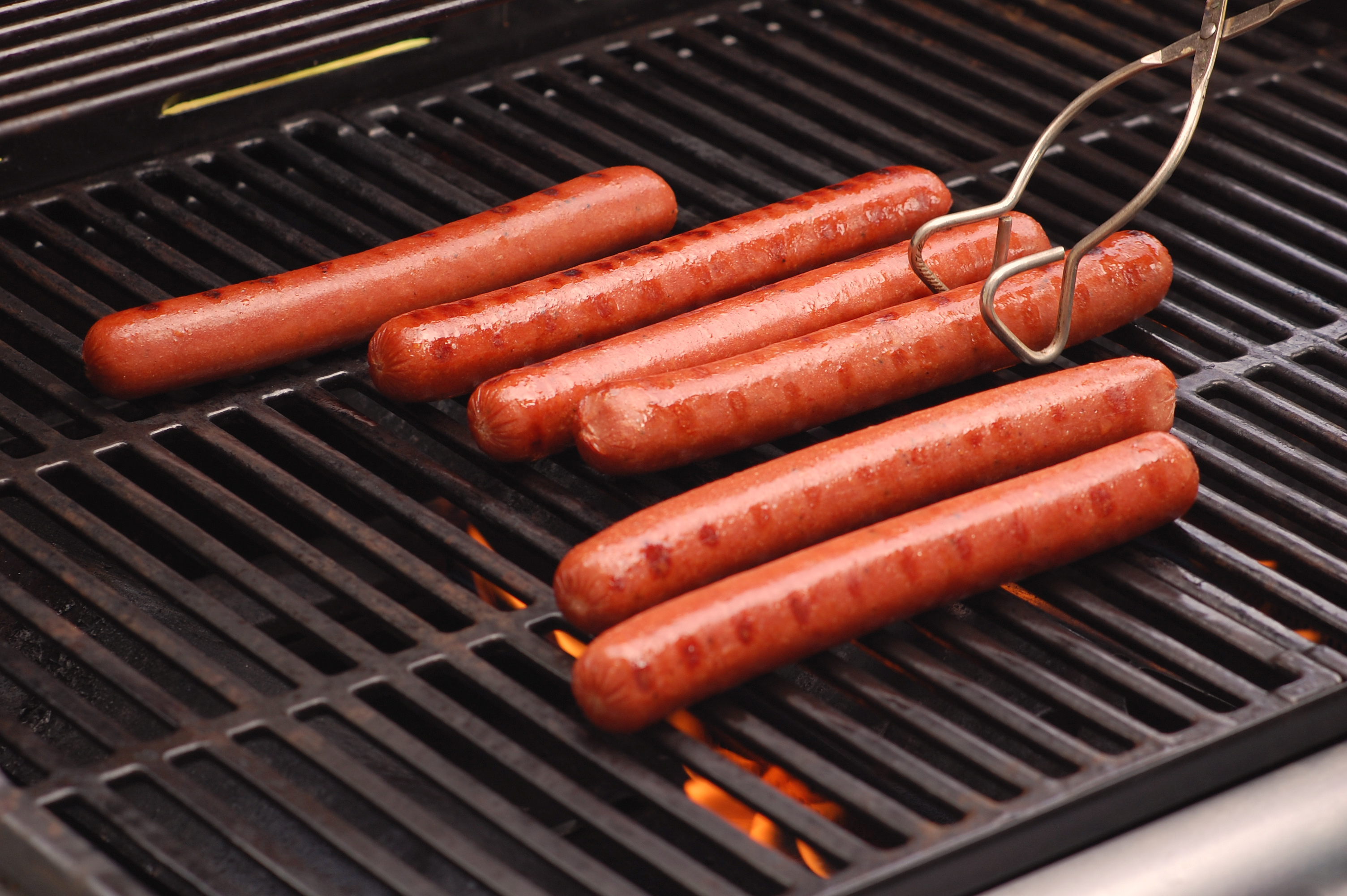 Six hot dogs cooking on a gas-fired barbeque grill.