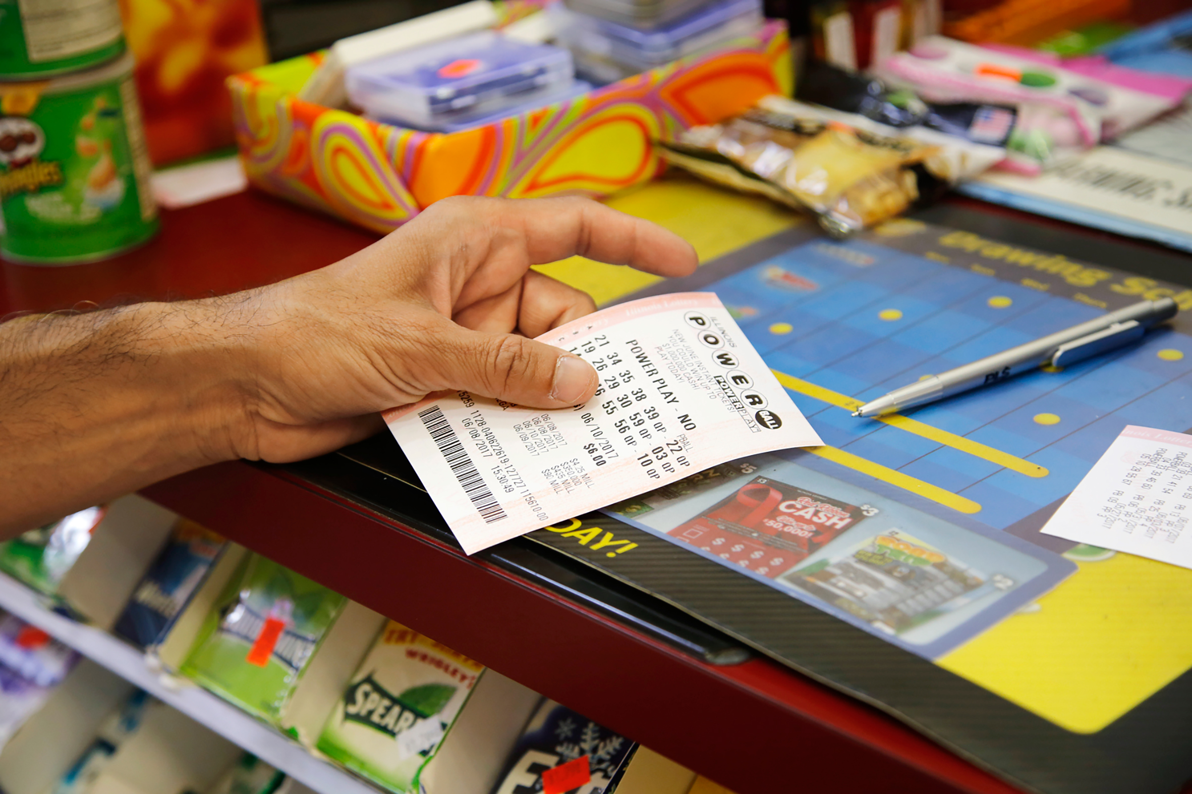 A customer buys a Powerball ticket, June 8, 2017, in Chicago.