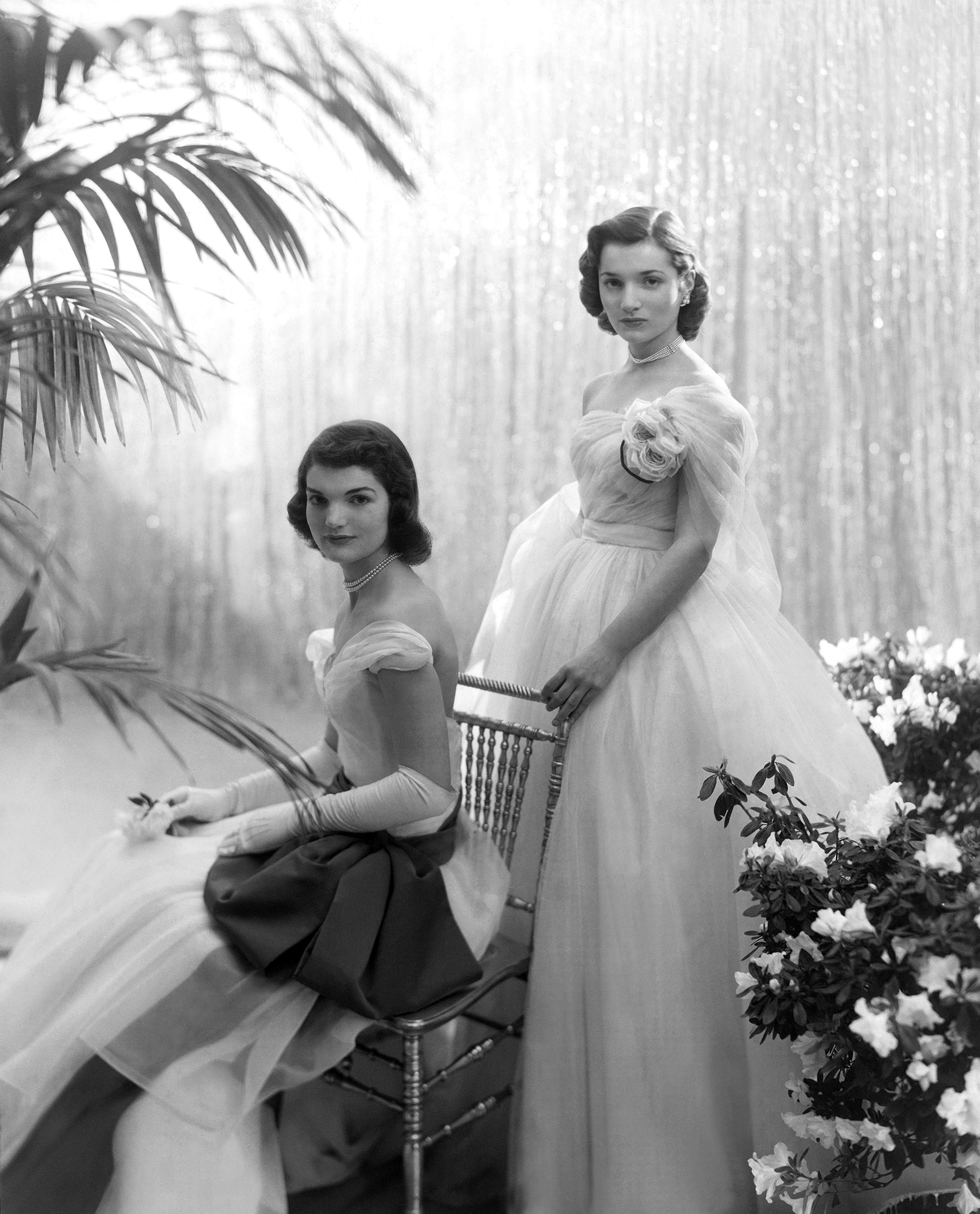 Jacqueline Bouvier (later Jacqueline Kennedy Onassis), seated, with her sister Caroline Lee Bouvier, standing behind her, wearing ball gowns, 1951.