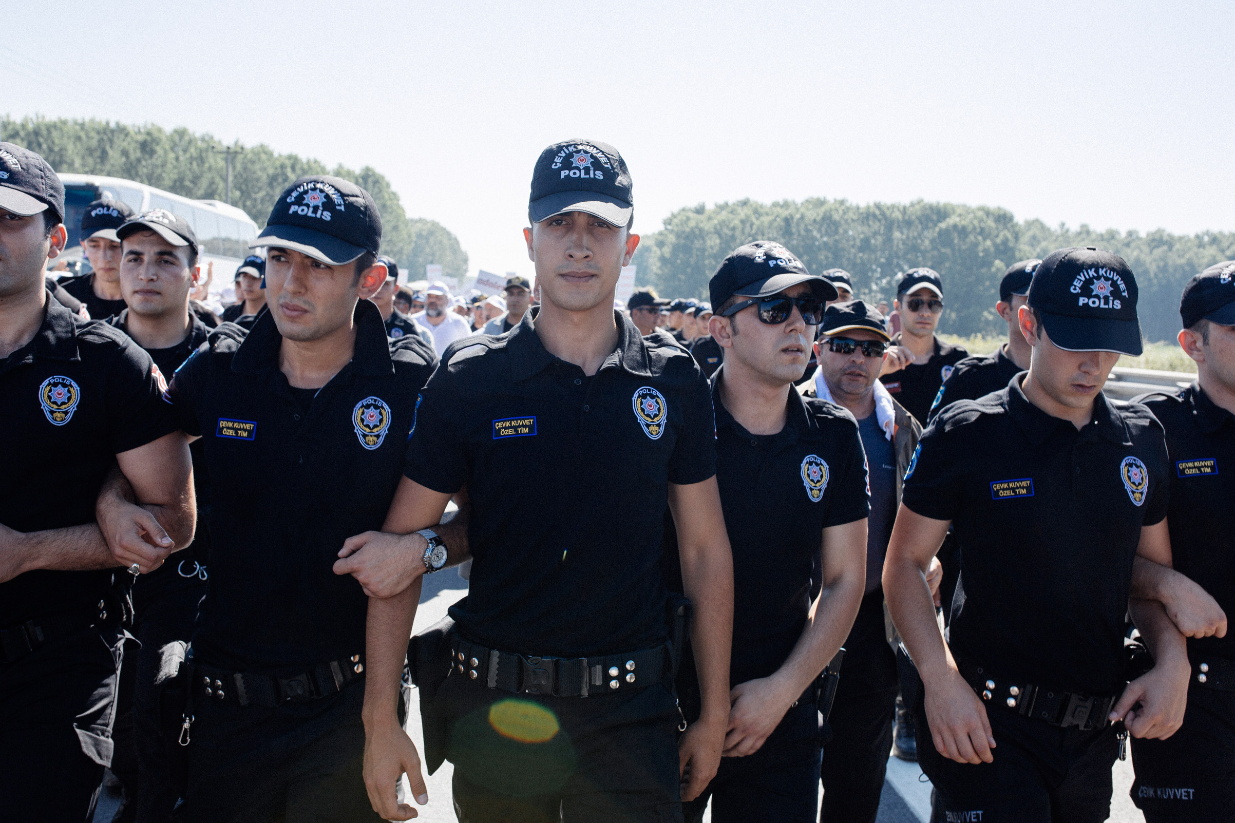 """Turkish police escort protestors during the Justice March in Hendek, Turkey, July 1, 2017. The leader of the march, Turkey's main opposition party CHP (Republican People's Party) leader Kemal Kilicdaroglu received threats after starting the walk June 15, 2017 in Ankara. President Erdogan accused Kilicdaroglu of staging """"protests to protect terrorists and those who support terrorism.   Responding to Erdogan's accusations, Kilicdaroglu said they were """"fitting for a dictator""""."""