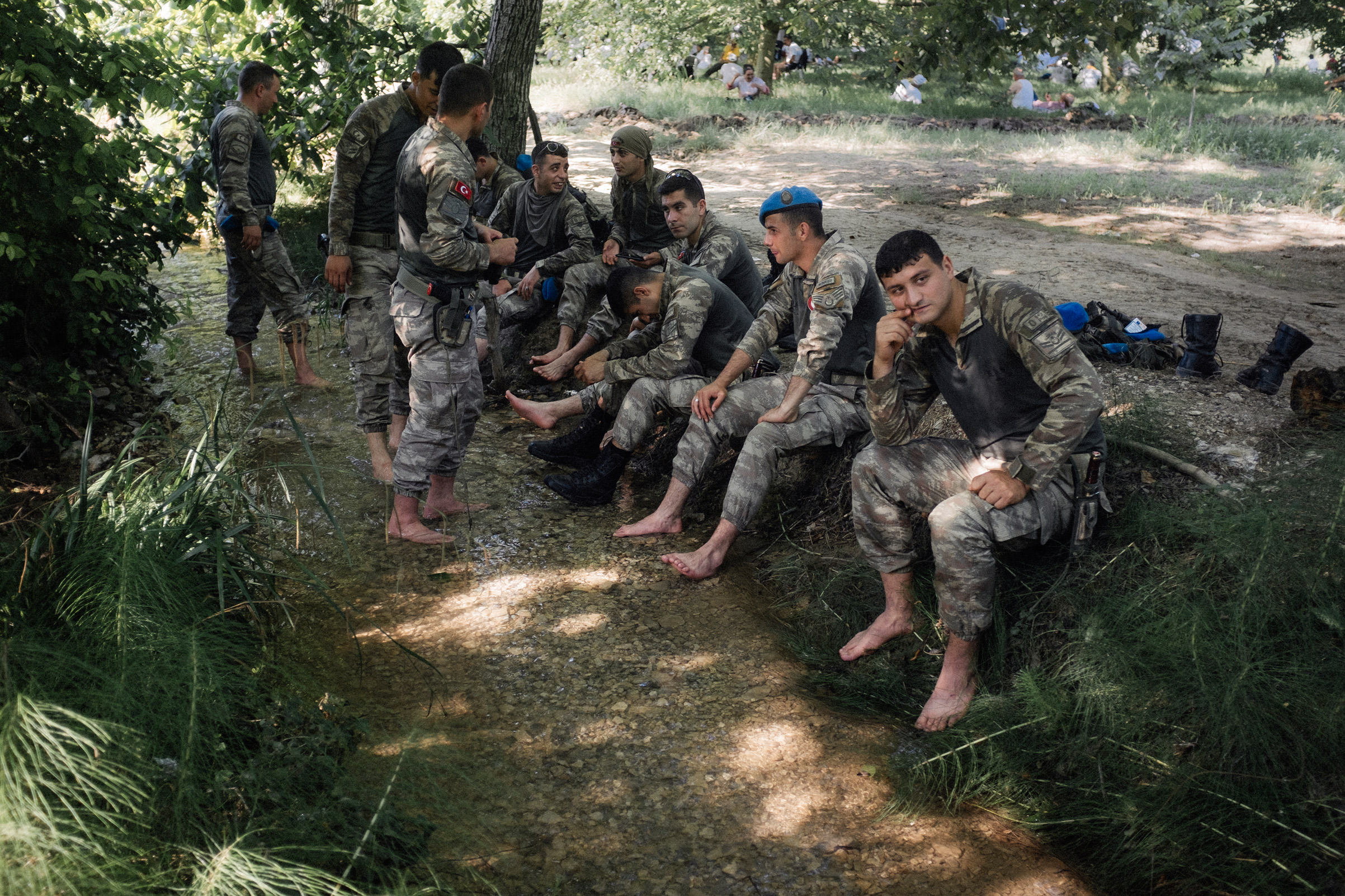 Turkish soldiers rest near a stream. Participants in the Justice March from Ankara to Istanbul also take a break nearby, Sakarya, Turkey, July 2, 2017.