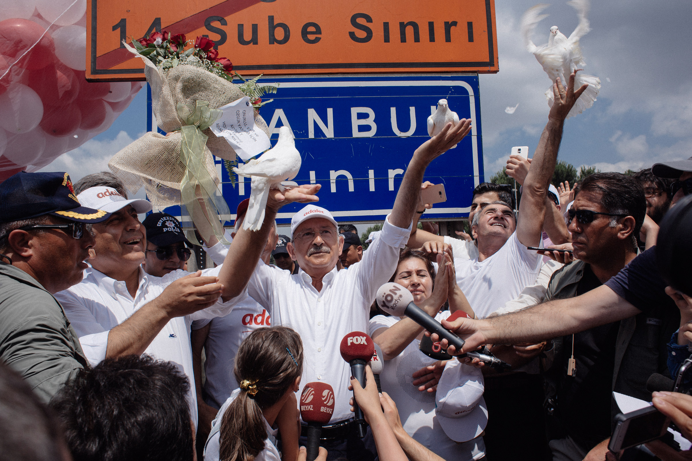 The head of Turkey's secularist Republican People's Party (CHP), Kemal Kilicdaroglu, enters Istanbul with thousands of supporters after the walking from Ankara leading the Justice March. He stands near the sign for the city where he released doves.