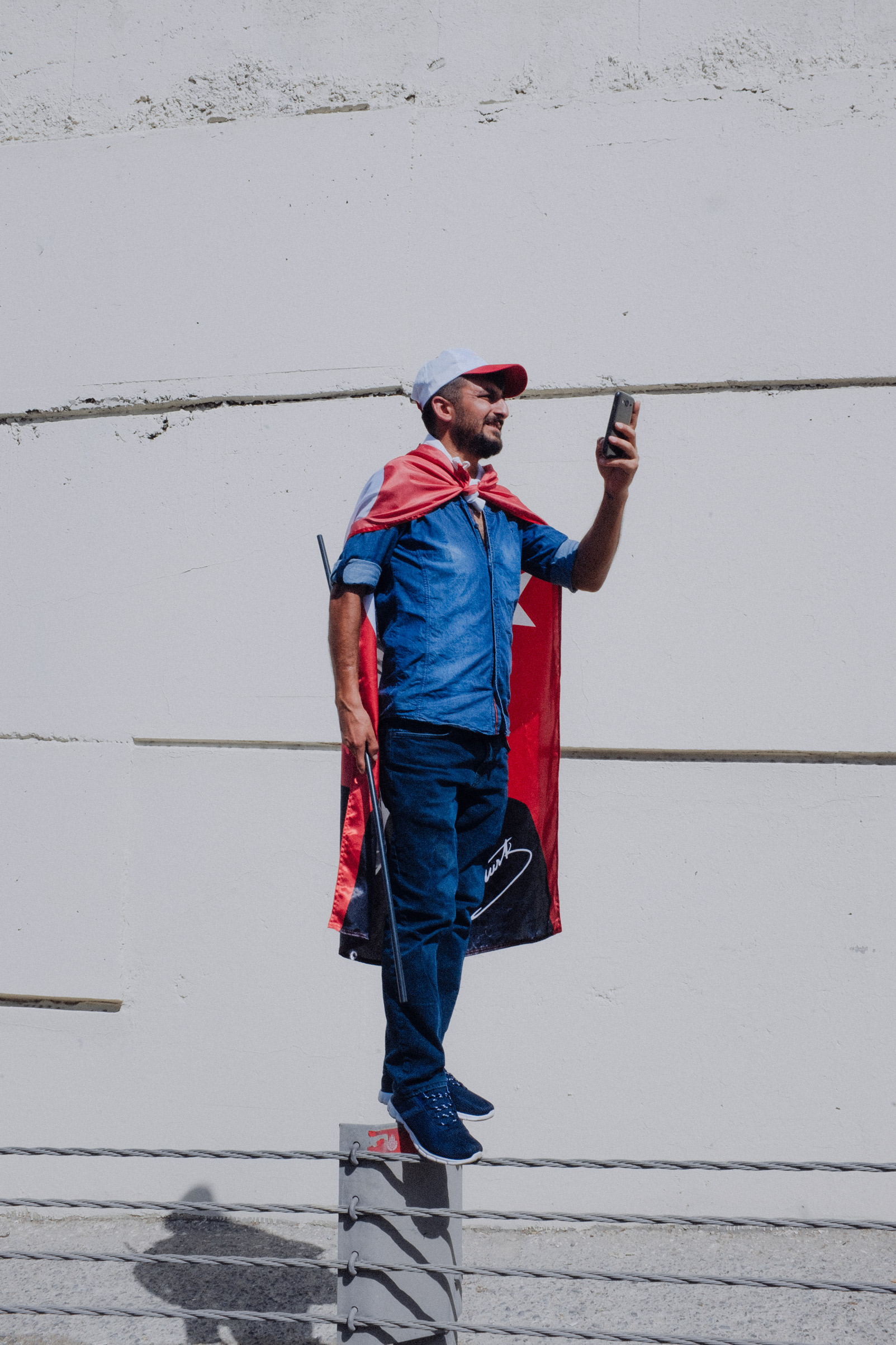 A man wearing  a Turkish flag records the Justice March with his mobile phone near the highway, as they enter Istanbul after 3 weeks of walking from Ankara to protest the more then 47,000 people who have been arrested by the government of President Recep Tayyip Erdogan over the last year since the attempted coup of July 15, 2016.