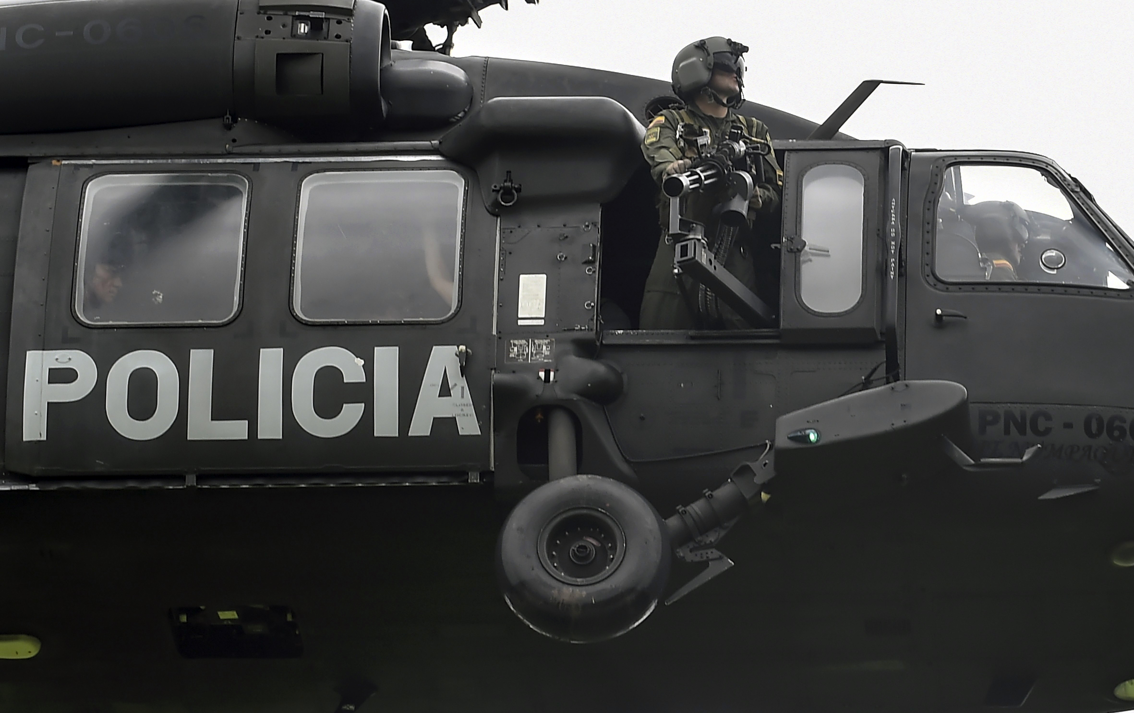 A helicopter used by Colombia's anti-narcotics police to throw pamphlets offering rewards for information leading to the capture of members of the Gulf Clan cartel overflies Apartado in Antioquia department, Colombia as part of the Agamemnon anti-drug trafficking operation on May 31, 2017.