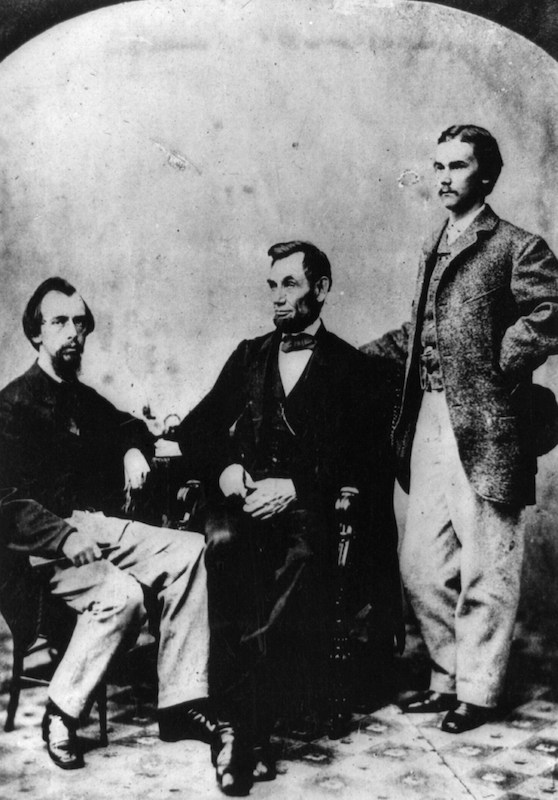 President Arbraham Lincoln, center, with his secretaries in 1863. John Hay is seen standing at right.