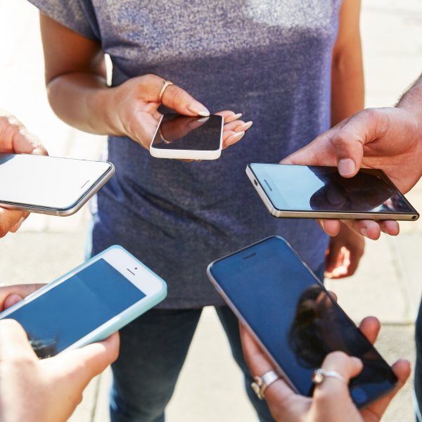 5 friends with smartphones, close up.