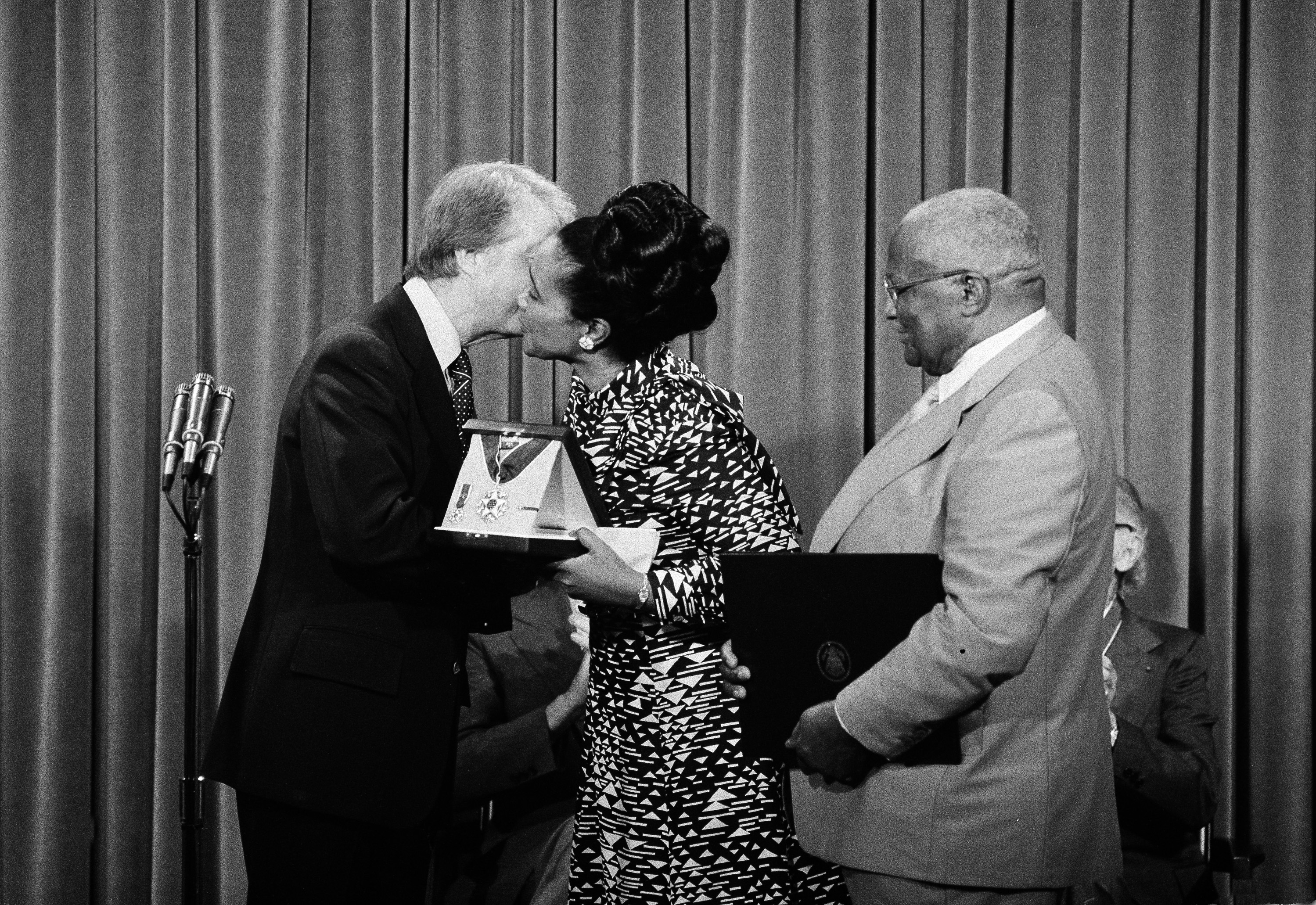 President Carter kisses Coretta Scott King, widow of civil rights leader Dr. Martin Luther King, Jr., at the White House, July 12, 1977, after he presented the Medal of Freedom to her on behalf of her late husband.