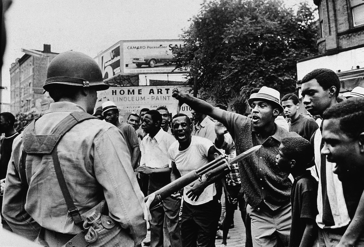 A back man gestures with his thumb down to an armed National Guardsman, during a protest in the Newark race riots, July 14, 1967.