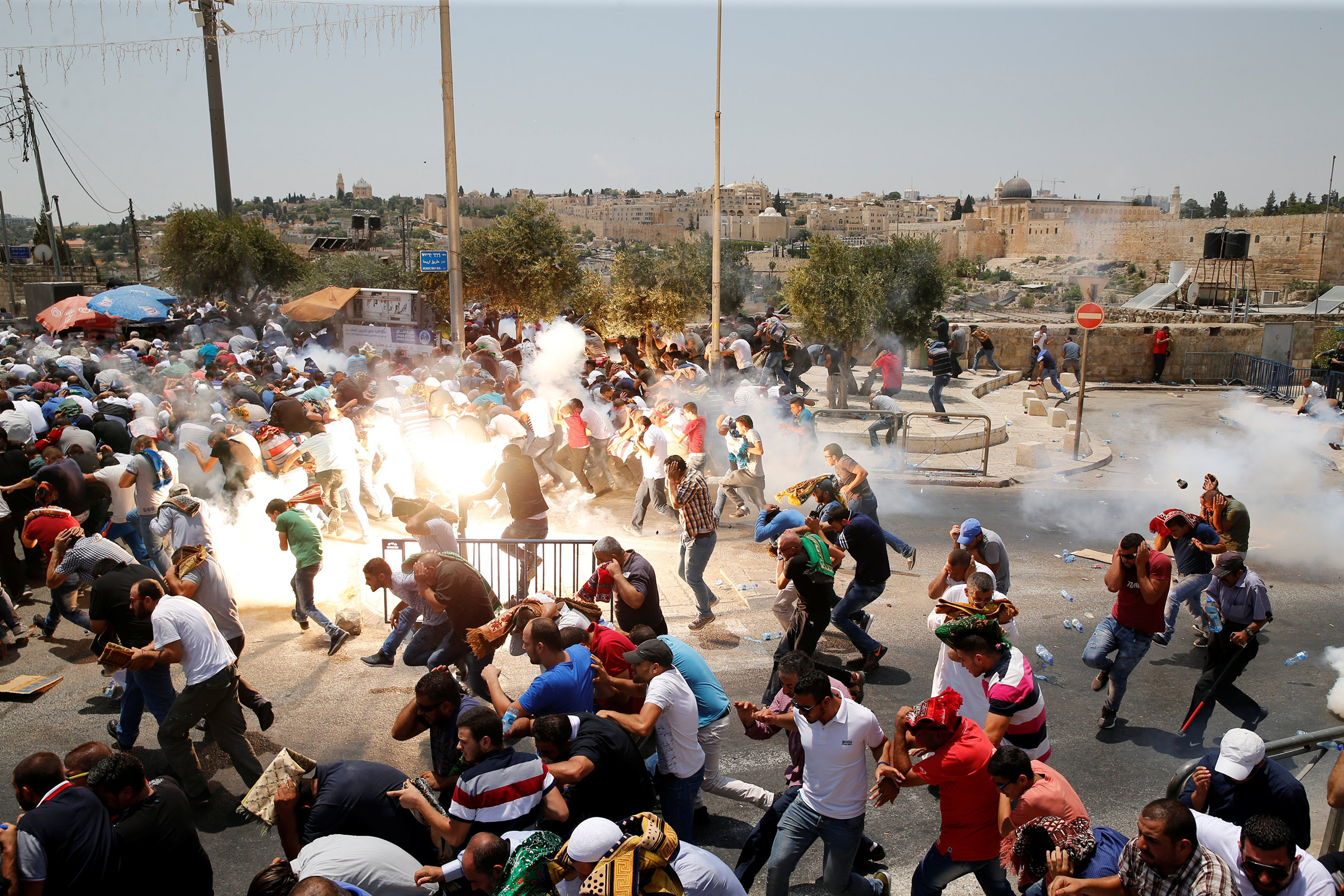 Palestinians react after tear gas was shot by Israeli forces after Friday prayers on a street outside Jerusalem's Old City on July 21, 2017.