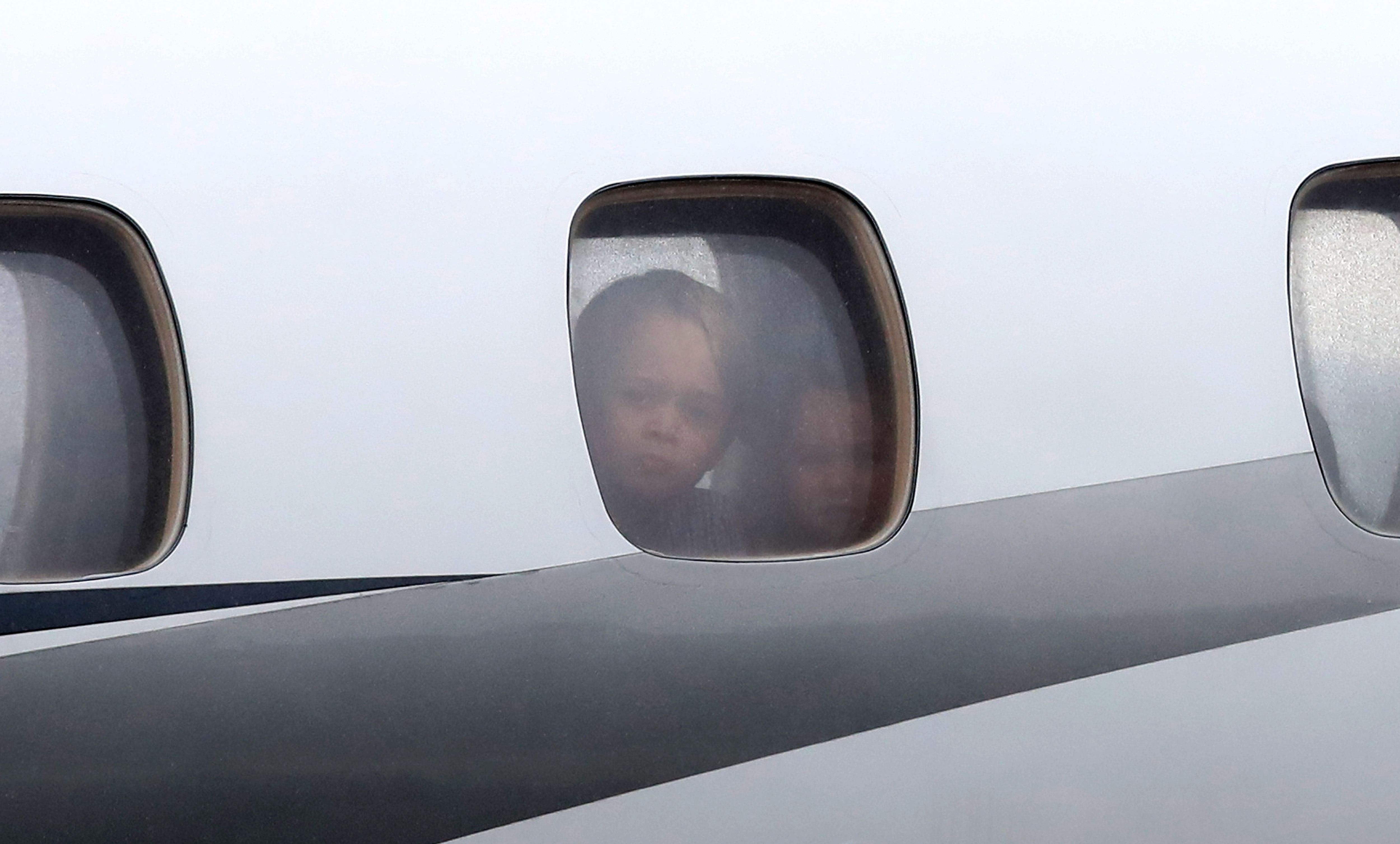 Prince George of Cambridge and Princess Charlotte of Cambridge peer out of a window as they arrive with Prince William, Duke of Cambridge and Catherine, Duchess of Cambridge on day 1 of their official visit to Poland.