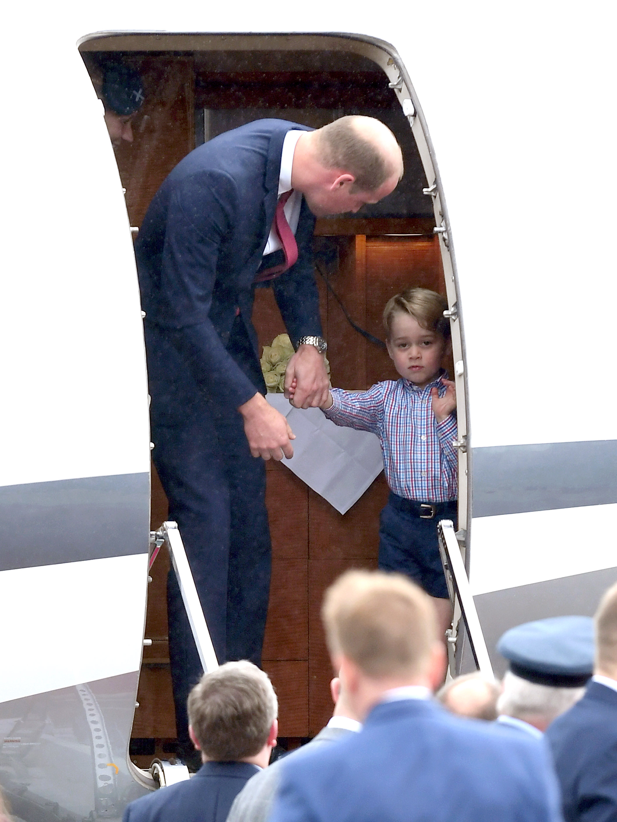 William leads George out of the plane at the Warsaw airport.