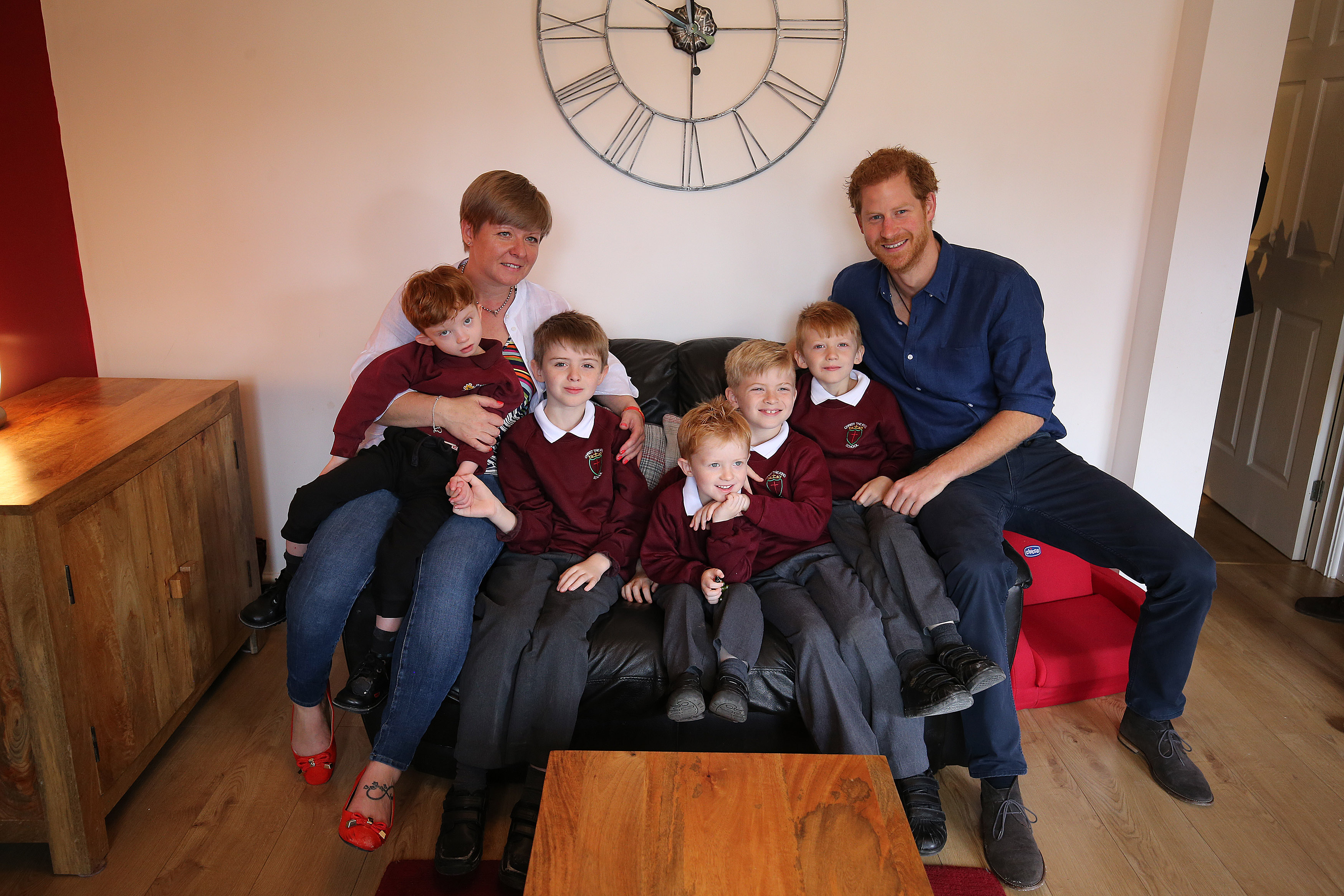 Britain's Prince Harry meets Oliver Rooney (L) who has Wolf Hirschhorn Syndrome with mum Elizabeth and brothers Samuel, Jack, Joseph and Thomas who are recieving a garden make over from WellCild at their home in Bramley during an official visit to Leeds on July 7, 2017 in Leeds, England.