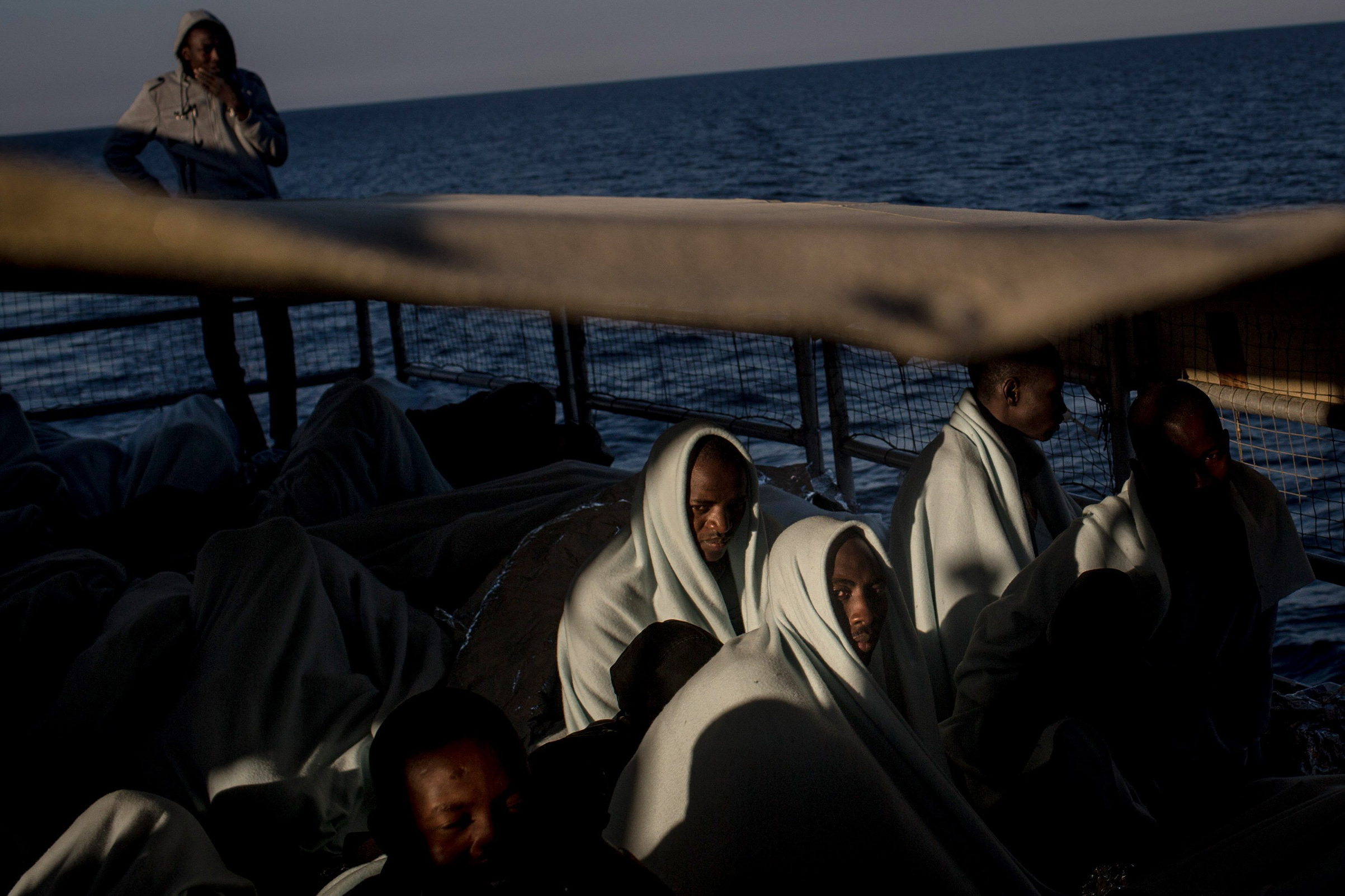 Refugees and migrants look out at Italy as they arrive on a Migrant Offshore Aid Station (MOAS) vessel to Reggio Calabria, Italy, on June 12, 2017.