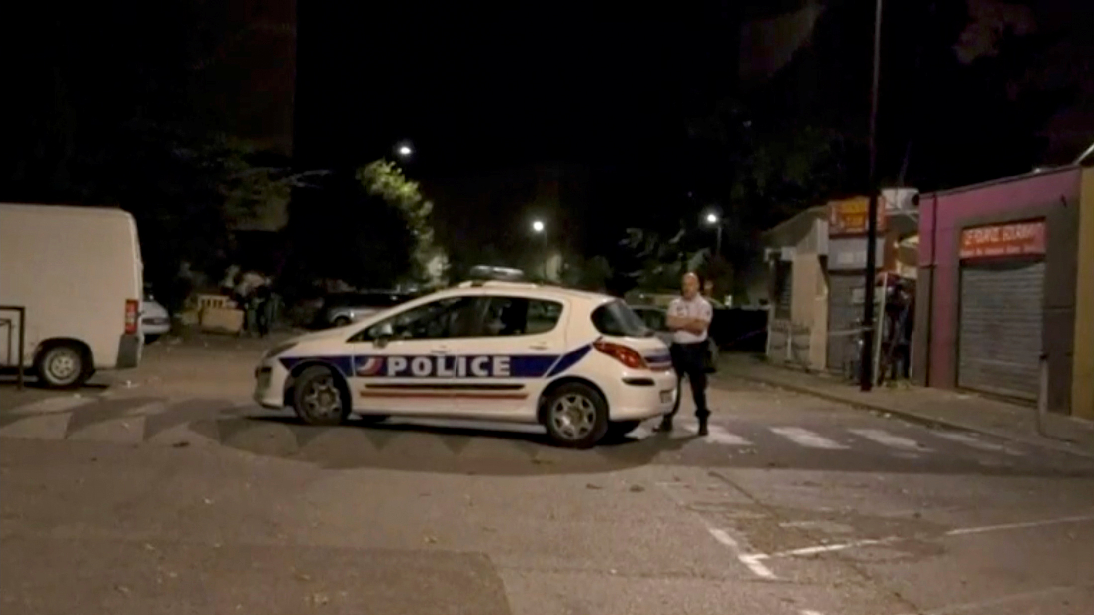 A police officer stands guard on a street near a scene of a shooting in front of a mosque, in this still image from video, in Avignon, France July 3, 2017.