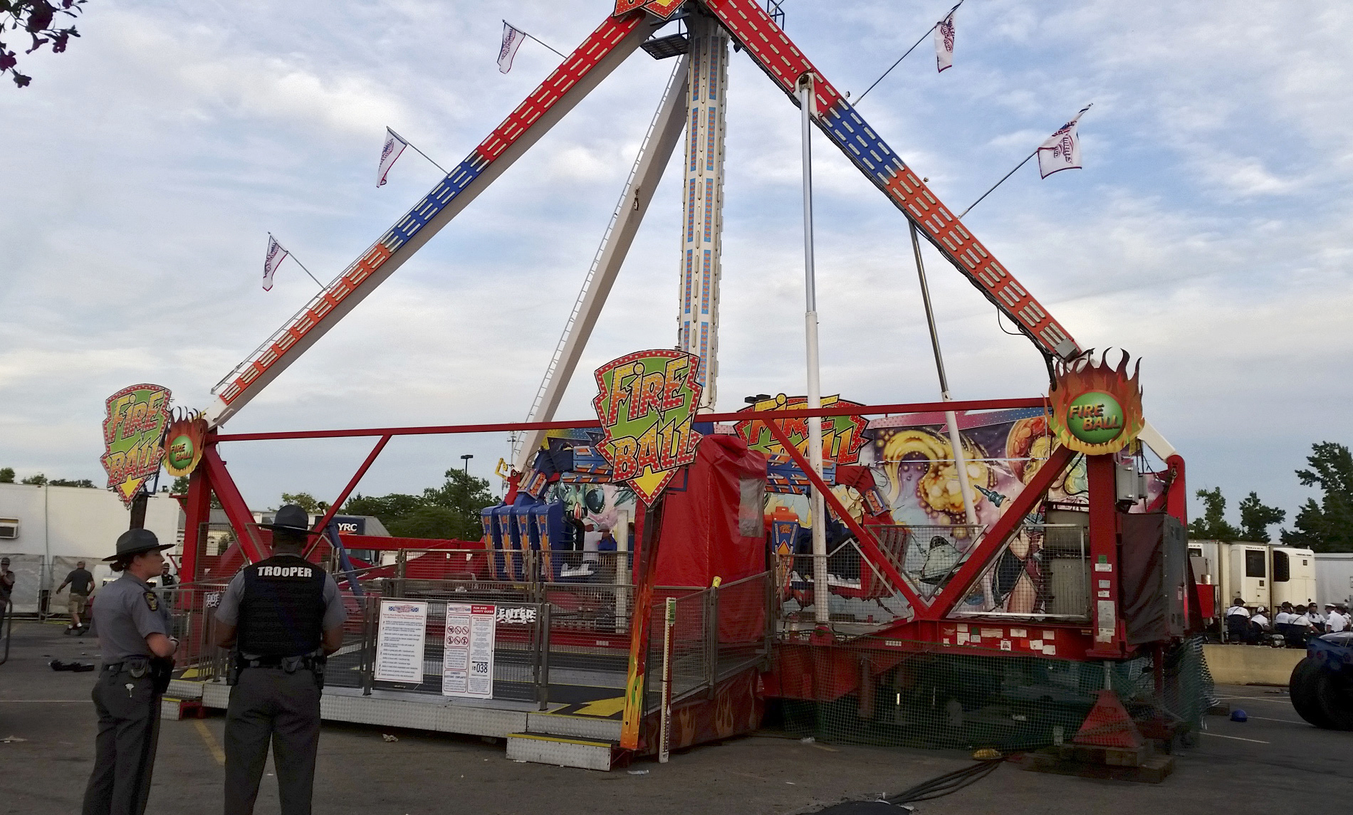 Authorities stand near the Fire Ball amusement ride after the ride malfunctioned at the Ohio State Fair, July 26, 2017, in Columbus, Ohio.
