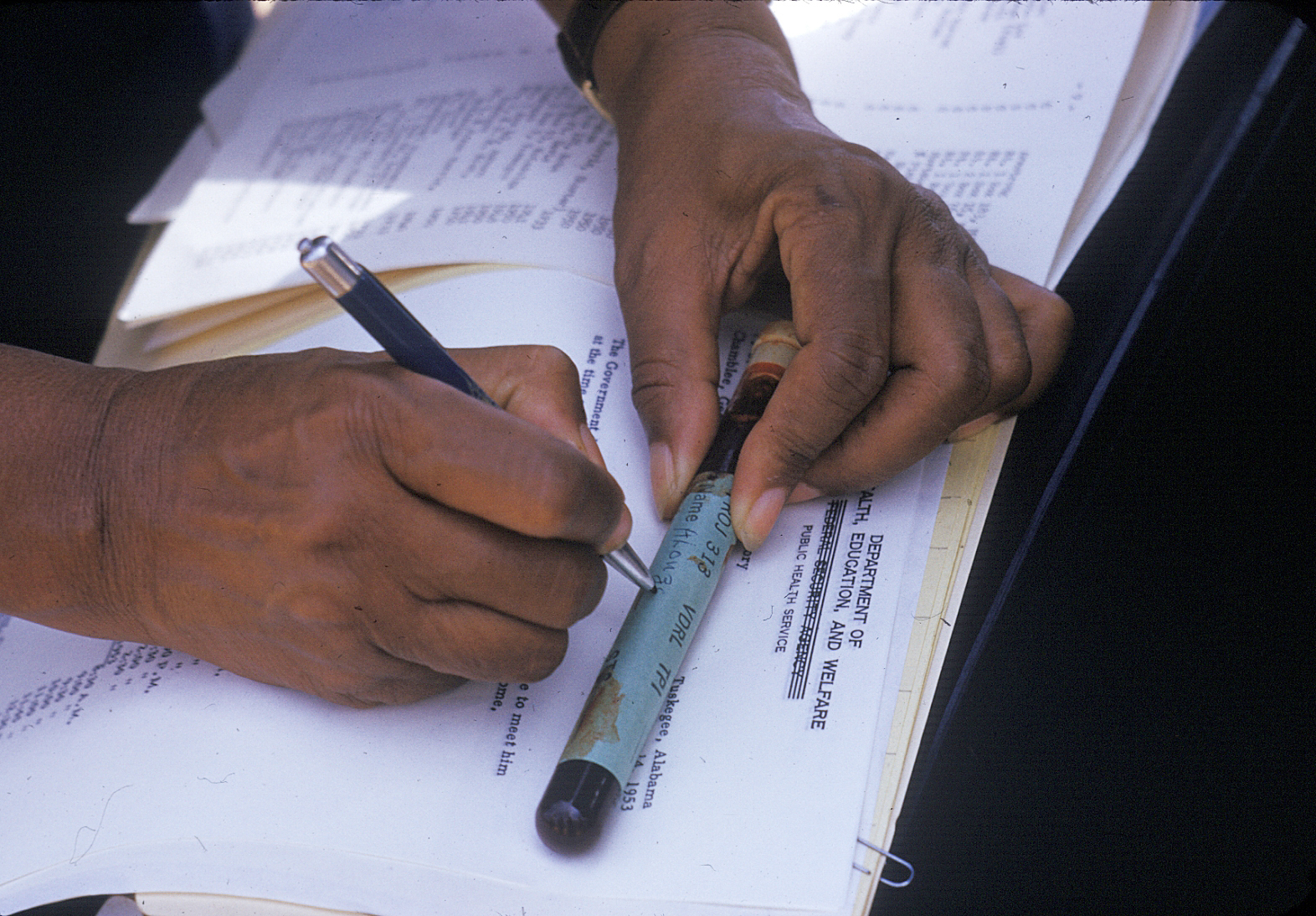 In this 1950's photo released by the National Archives, a nurse writes on a vial of blood taken from a participant in a syphilis study in Tuskegee, Ala.