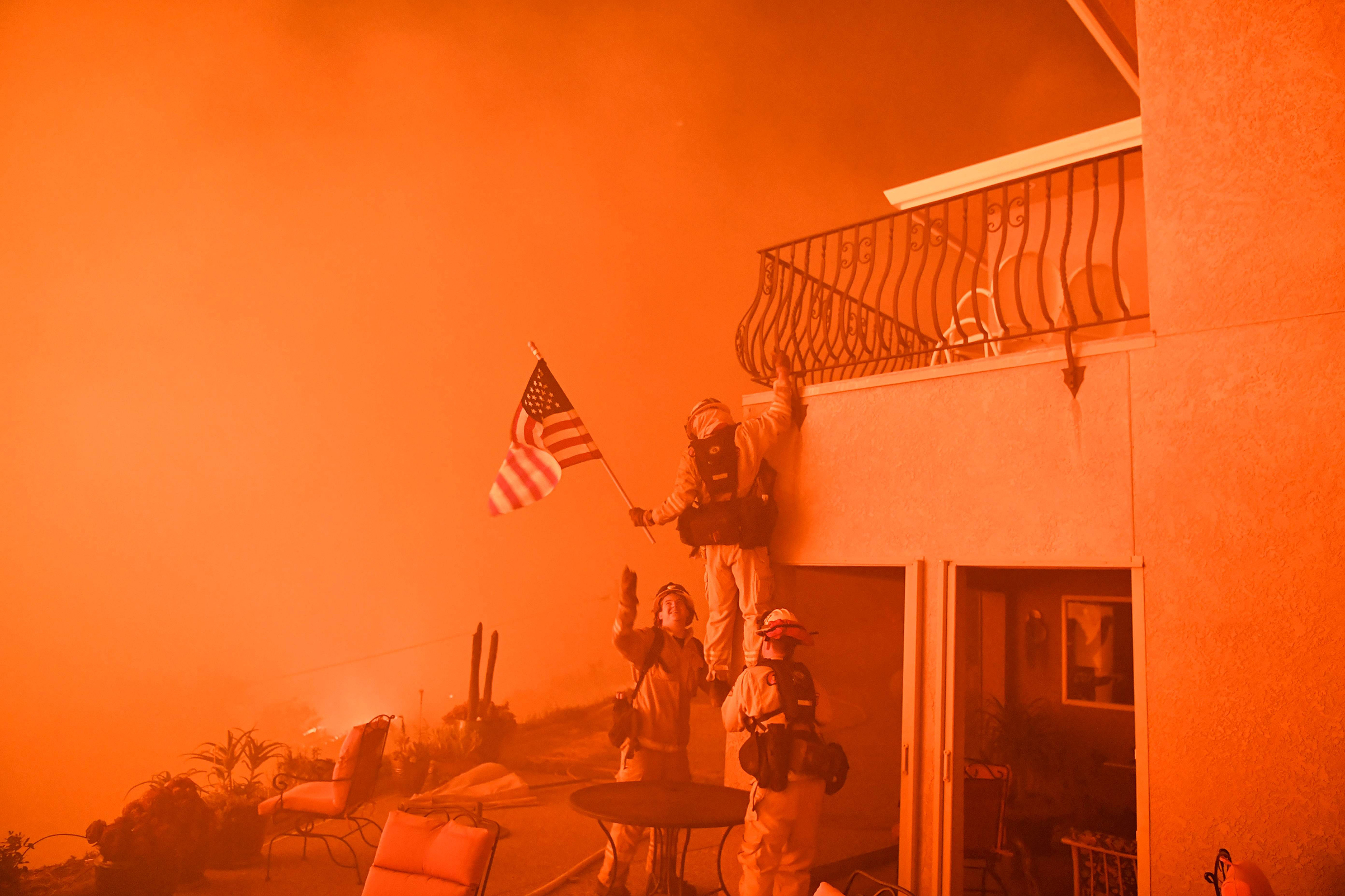 Firefighters save an American flag as impending flames from the Wall Fire close in on a luxury home in Oroville, Calif., on July 8, 2017.