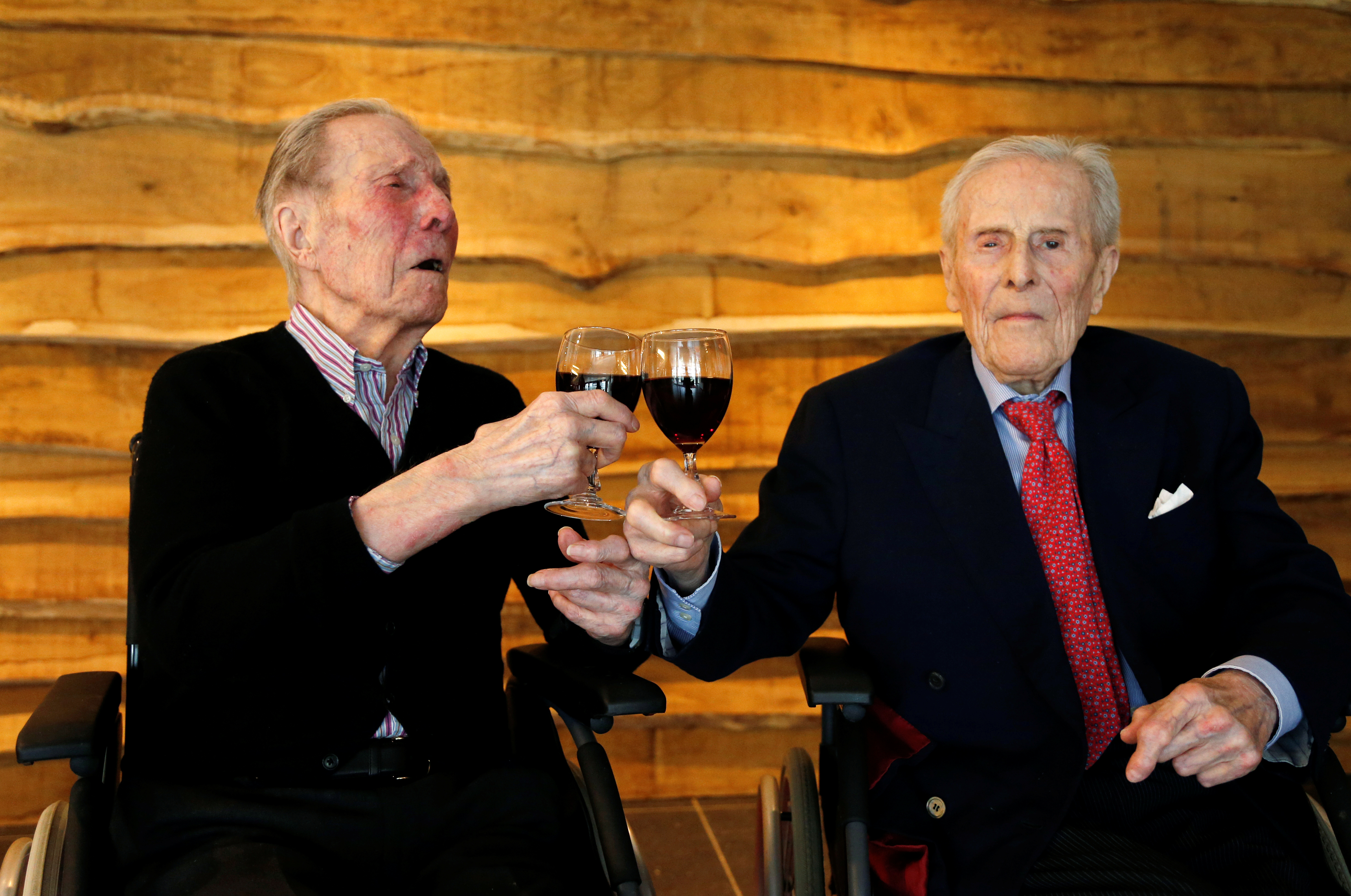 The world's oldest living twin brothers, Paulus (L) and Pieter Langerock from Belgium, 102, toast with a glass of red wine at the Ter Venne retirement home in Sint-Martens-Latem, Belgium, July 4, 2016.