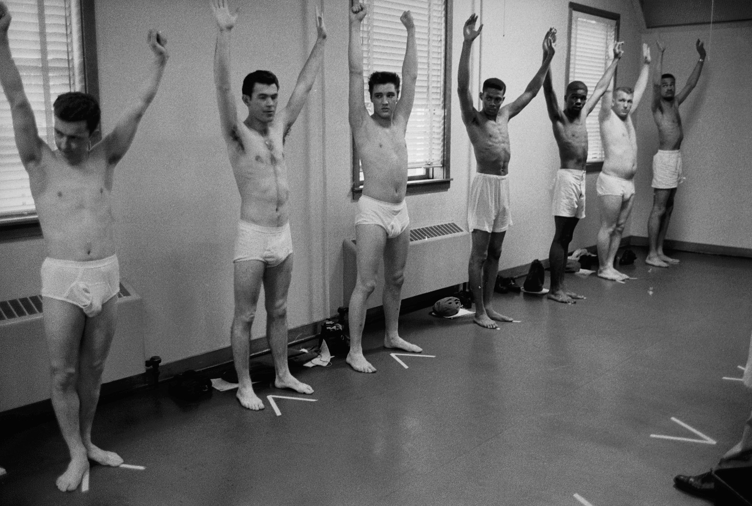 Wearing only underwear, singing star turned US Army Pvt. Elvis Presley (3L) raises his arms along w. several other inductees during an inspection at Ft. Chaffee, Alaska, March 1, 1958.
