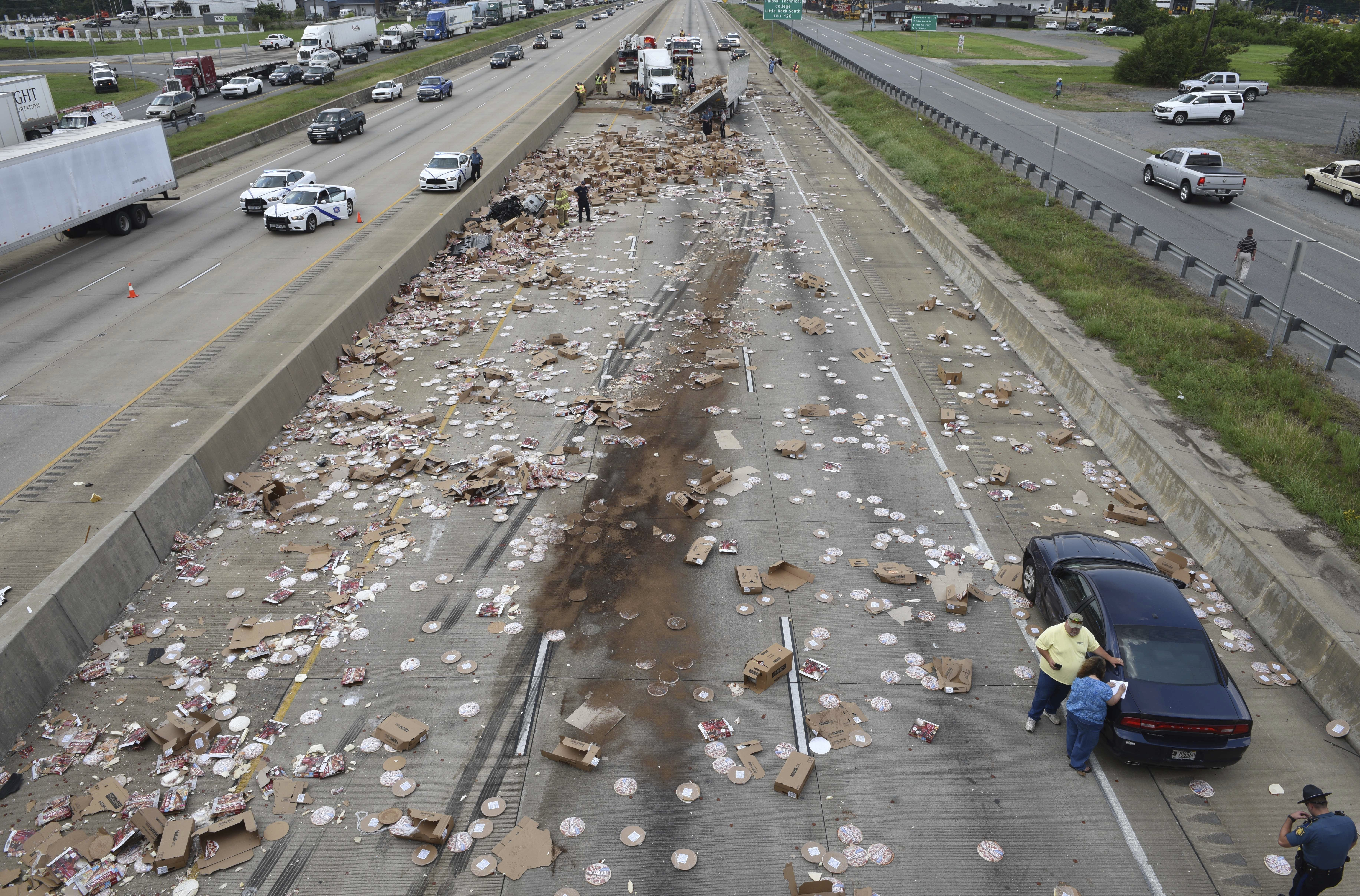 This Wednesday, Aug. 9, 2017, photo provided by the Arkansas Department of Transportation shows Arkansas highway Interstate 30, a cross-country route that was shut down in both directions for a time Wednesday, after an 18-wheeler was sliced open during an crash and spilled frozen pizzas across the road south of Little Rock, Ark.