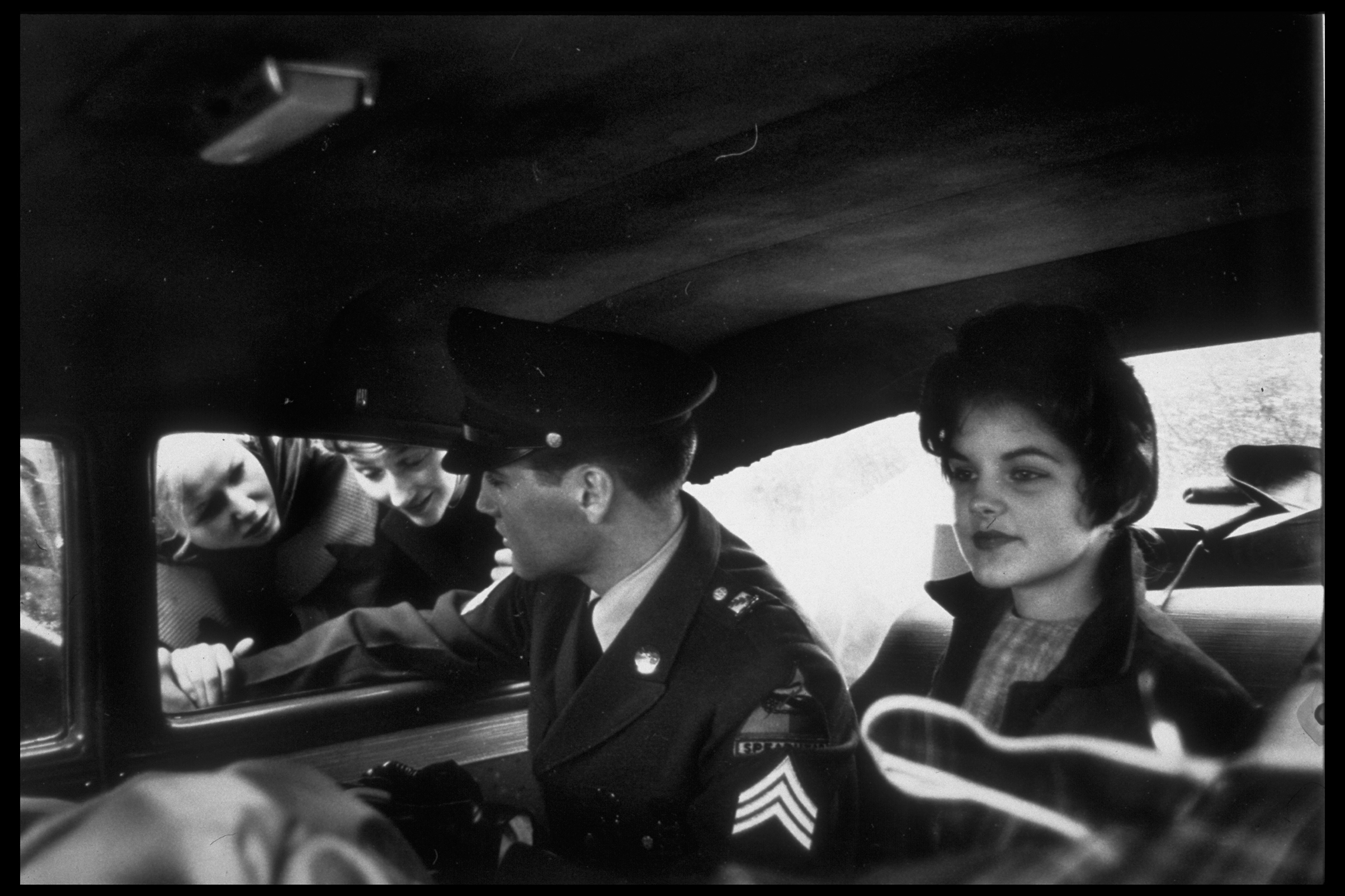 Rocker/Corporal Elvis wearing uniform while chatting w. fans through window as girlfriend Priscilla Beaulieu sits beside him in back seat of car, Germany, 1960.