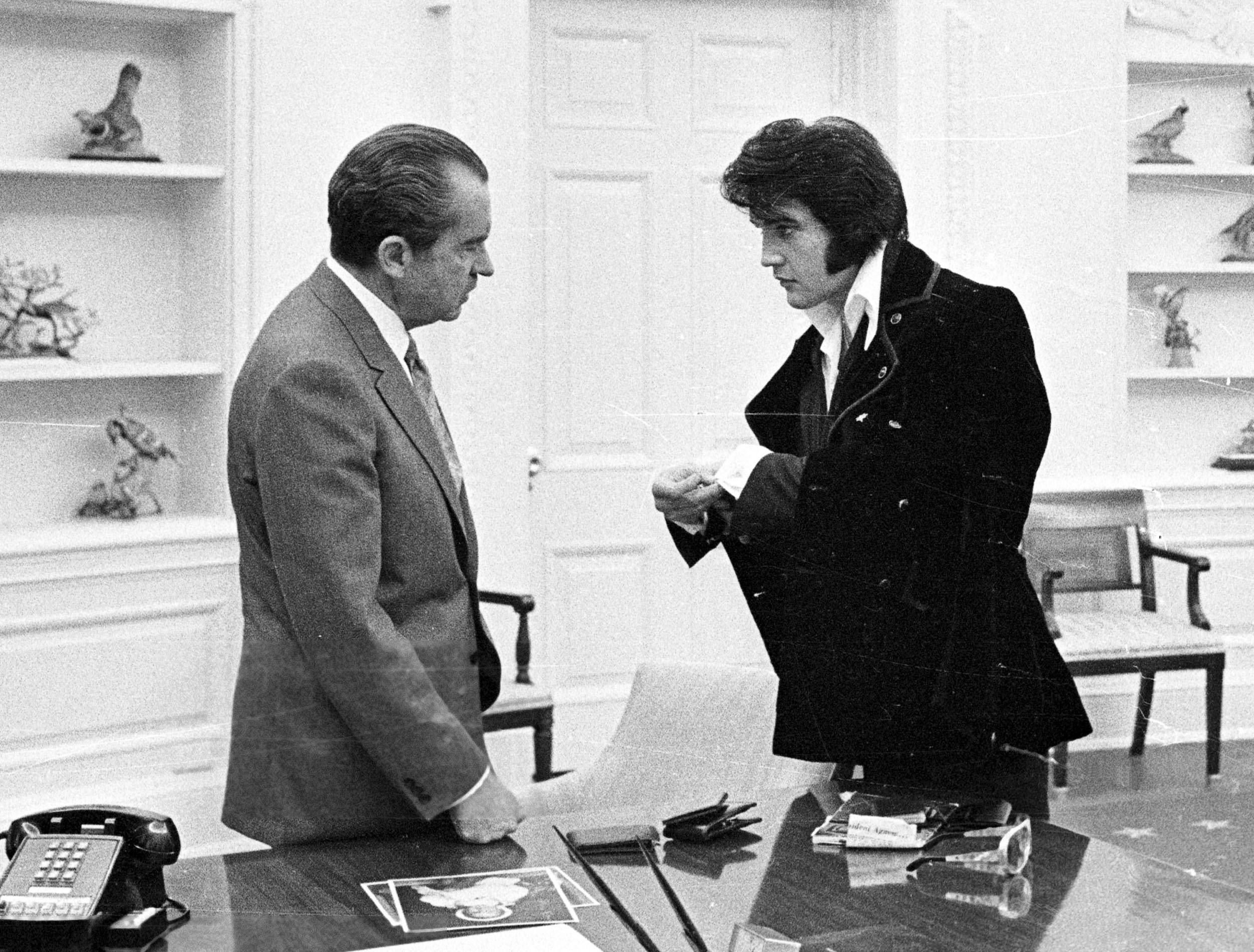 Elvis Presley shows President Richard Nixon his cuff links,  during a visit to the White House. Dec. 21, 1970.