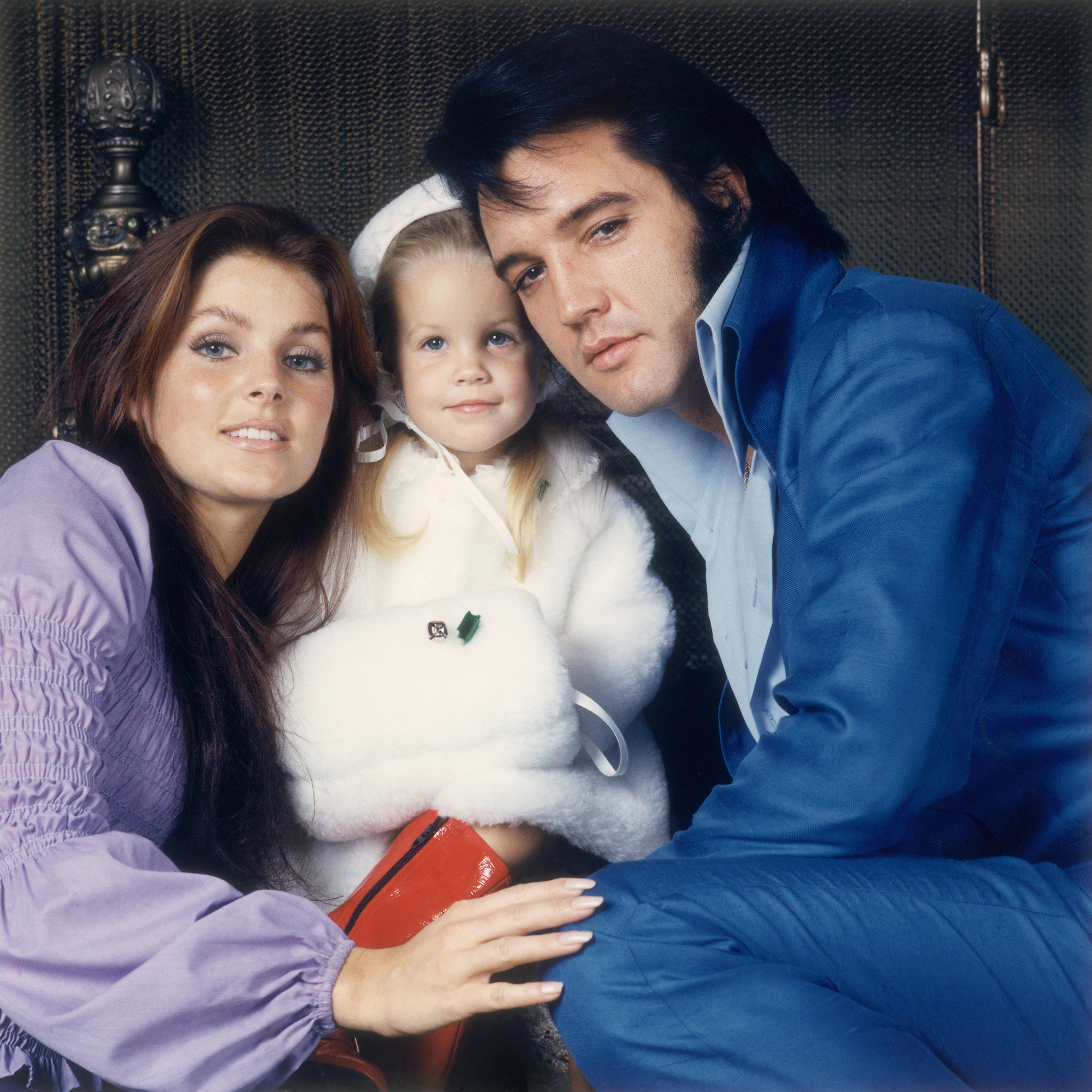 Elvis with his wife Priscilla and their daughter Lisa-Marie as they pose for a family portrait, 1970s.