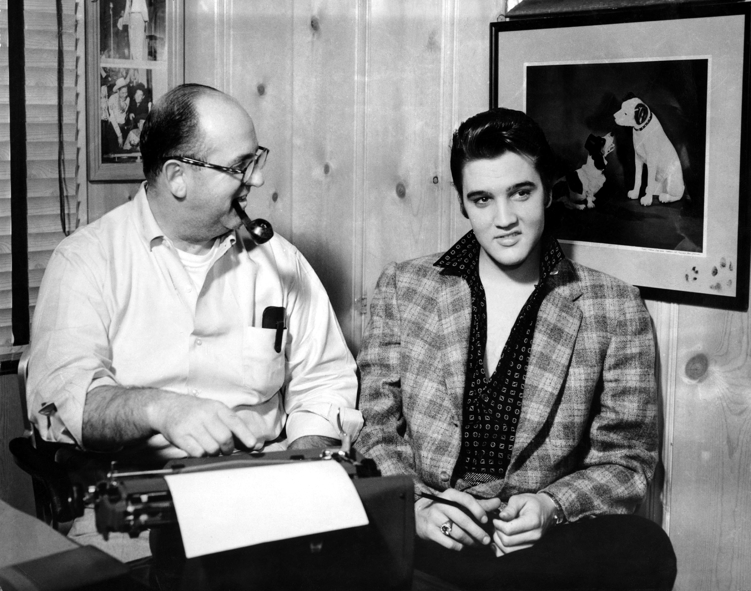 Elvis and his manager Colonel Tom Parker sit at a typewriter in front of the a picture of the RCA Victor Dog in circa 1956 in Memphis, Tenn.