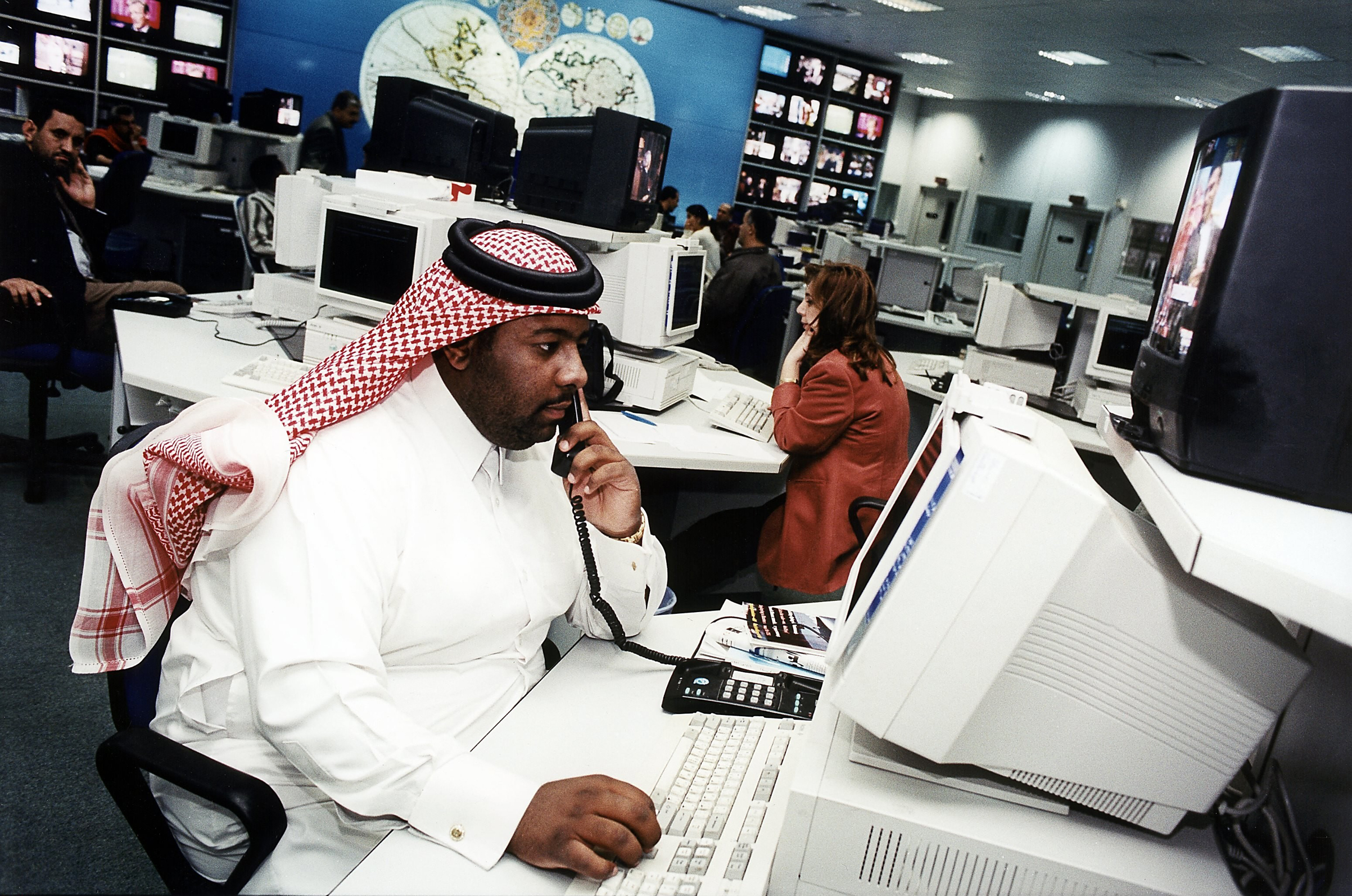 A journalist works in the Doha newsroom in April 2001.