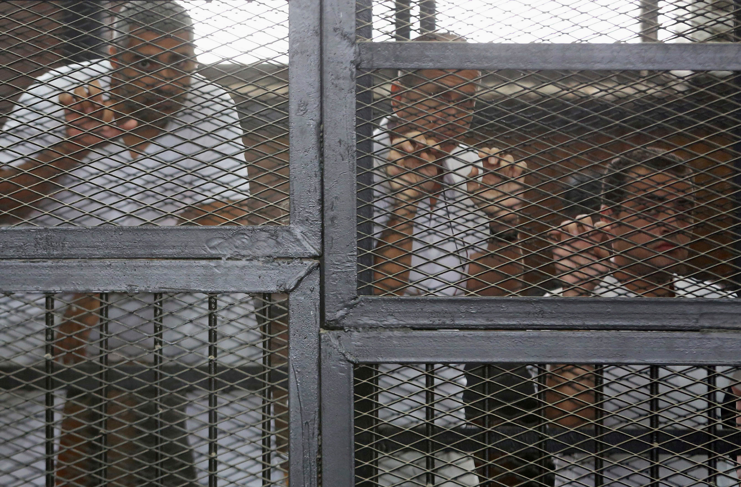 Al Jazeera journalists Mohammed Fahmy, Peter Greste and Baher Mohamed behind bars at a court in Cairo on May 15, 2014.