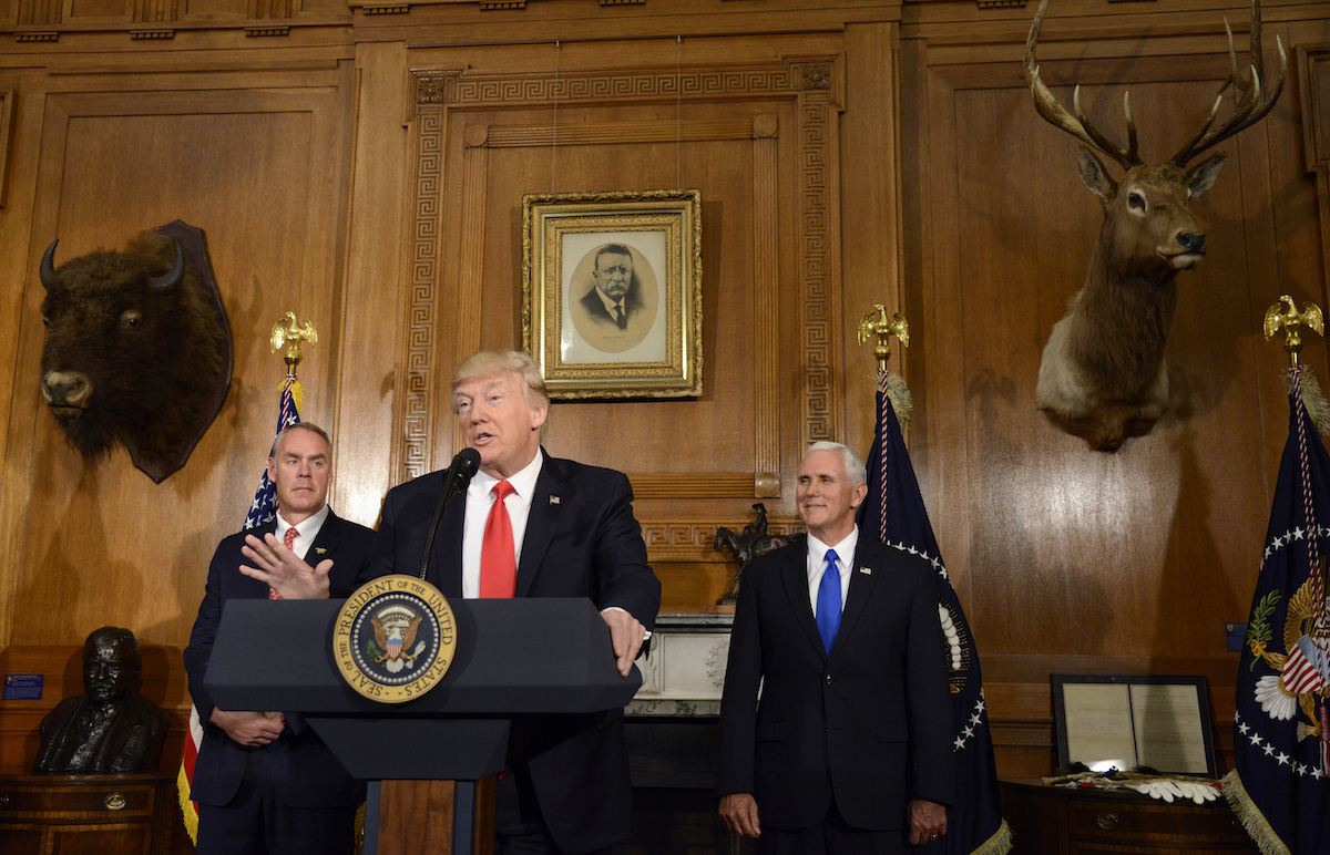 U.S. President Donald Trump, center, speaks while Ryan Zinke, U.S. secretary of interior, left, and U.S. Vice President Mike Pence before signing an executive order about the antiquities act at the Department of the Interior in Washington, D.C., April 26, 2017.