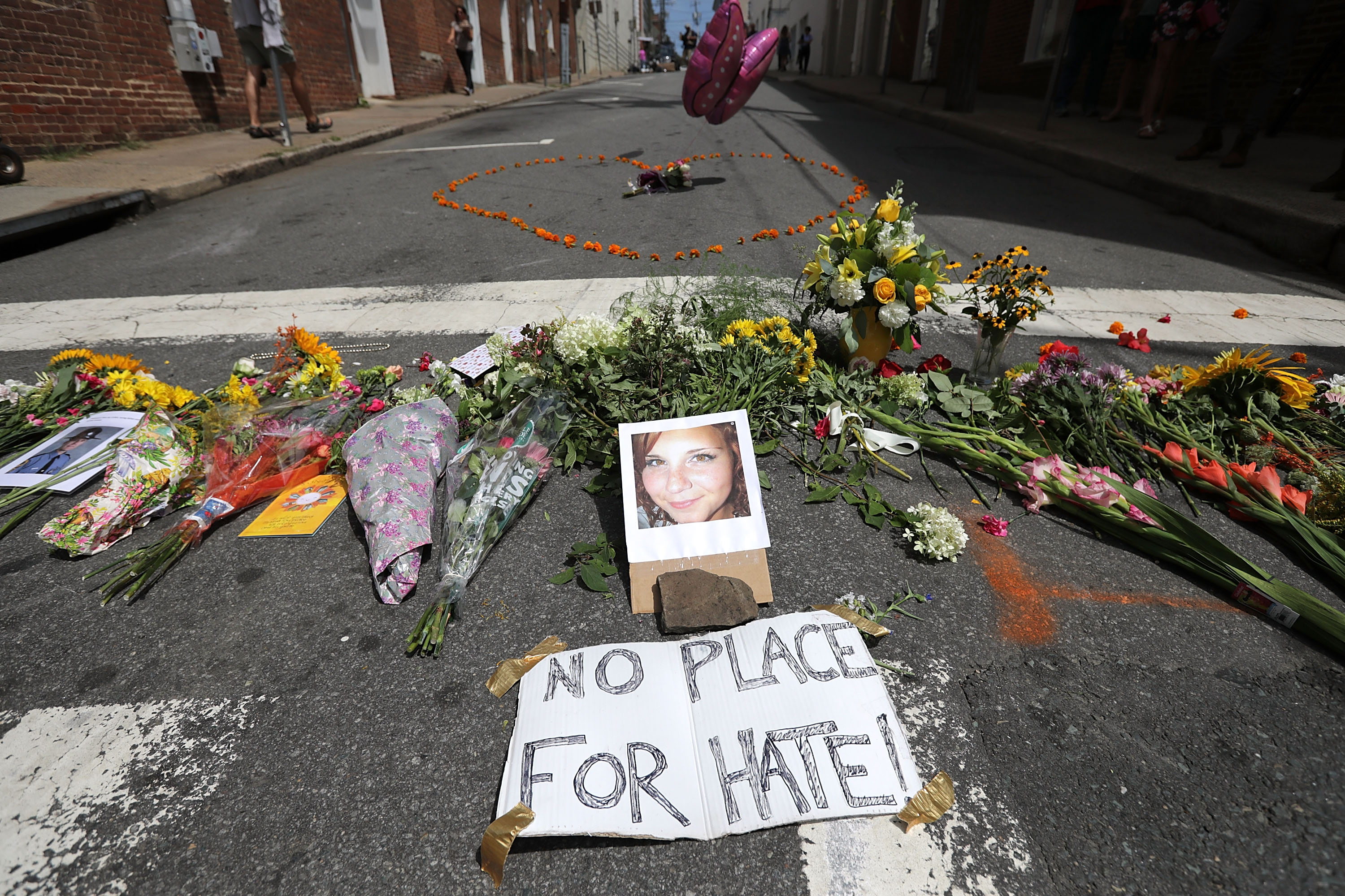 Flowers surround a photo of 32-year-old Heather Heyer, who was killed when a car plowed into a crowd of people protesting against the white supremacist Unite the Right rally, August 13, 2017 in Charlottesville, Va.